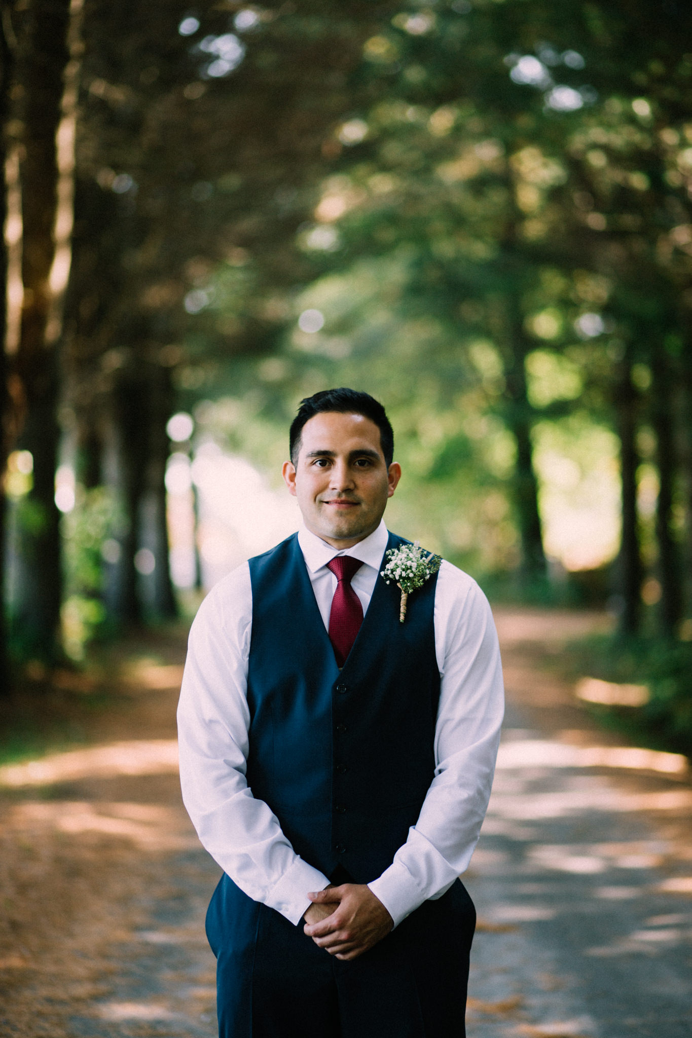 groom standing on a path in a forest