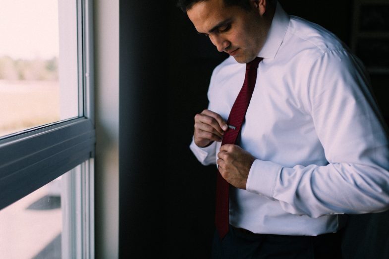 groom putting on tie bar