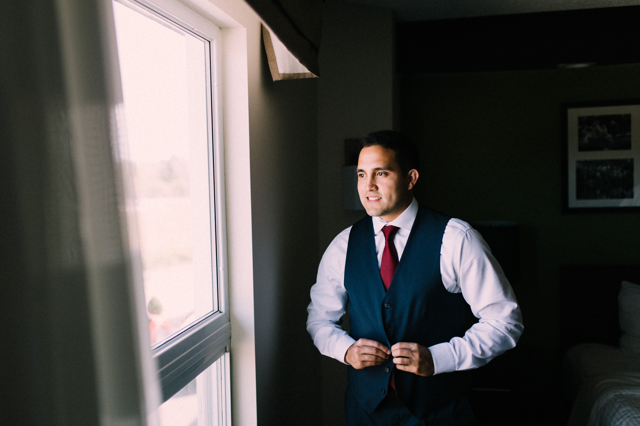groom buttoning up vest looking out the window