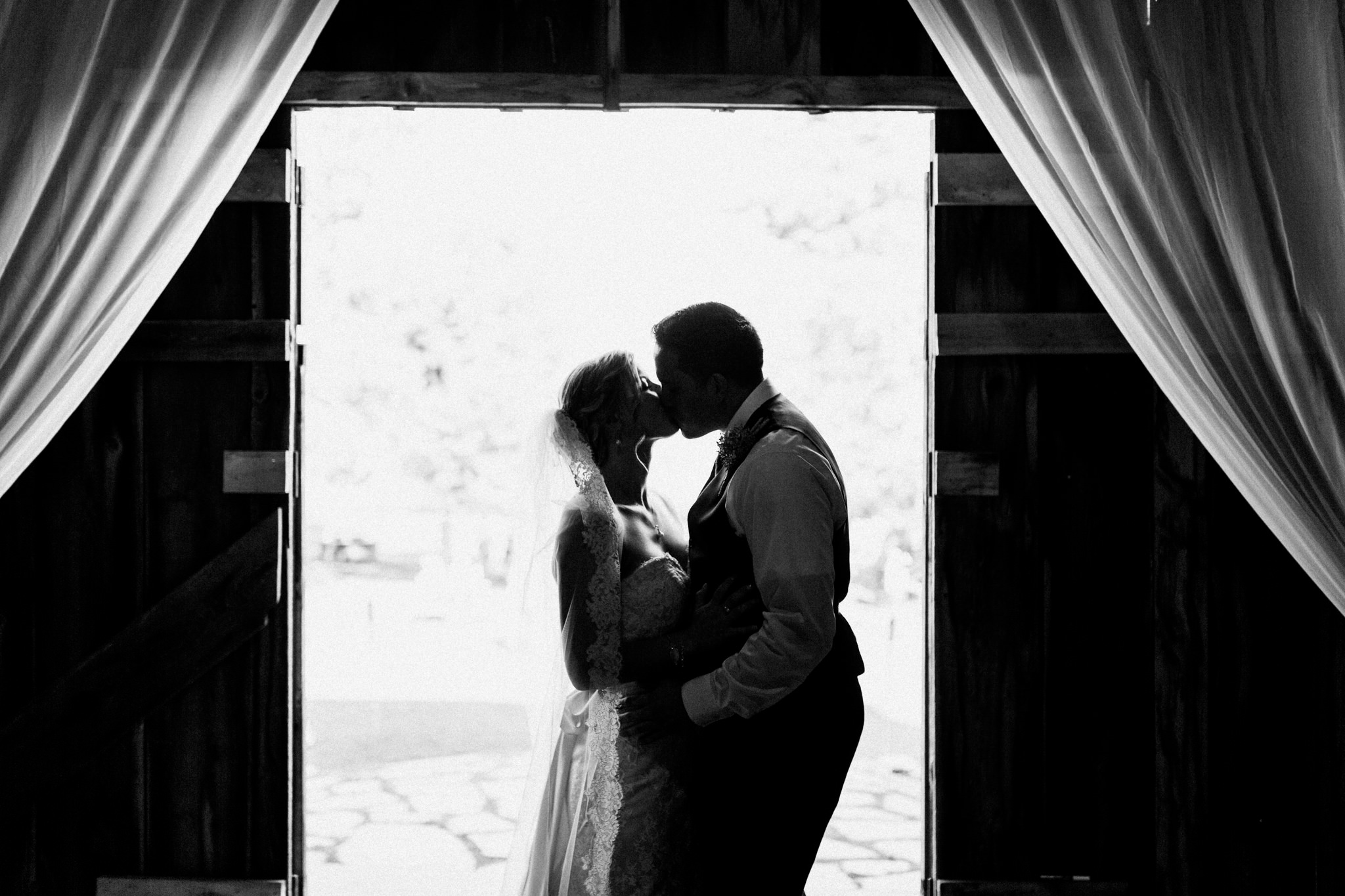 bride and groom kissing in the doorway of a barn