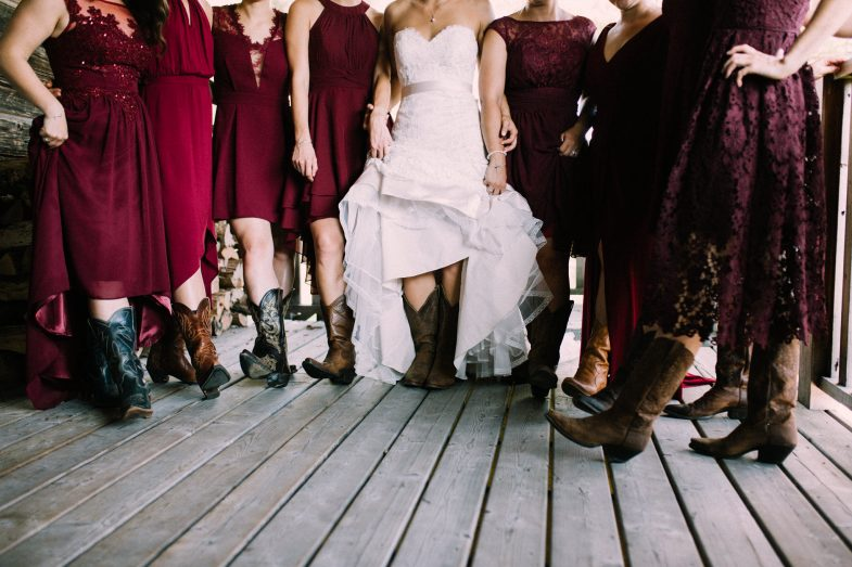 bridesmaids all wearing cowboy boots hiking up their dresses