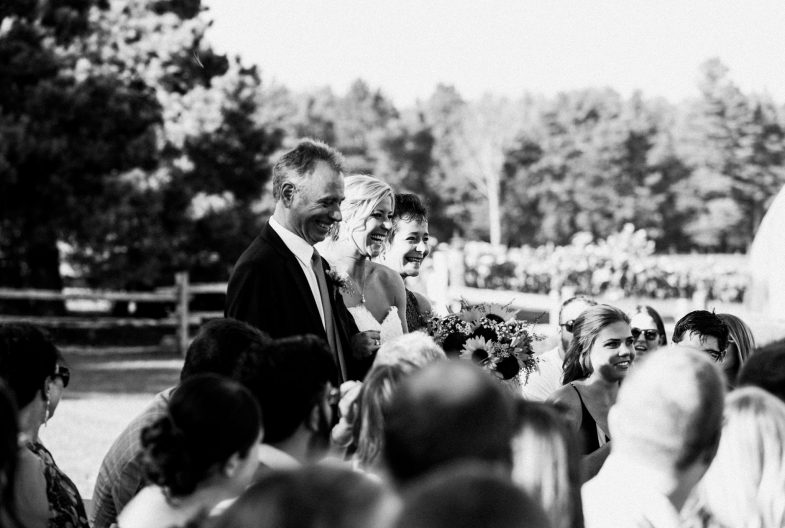 bride and parents smiling while walking down the aisle