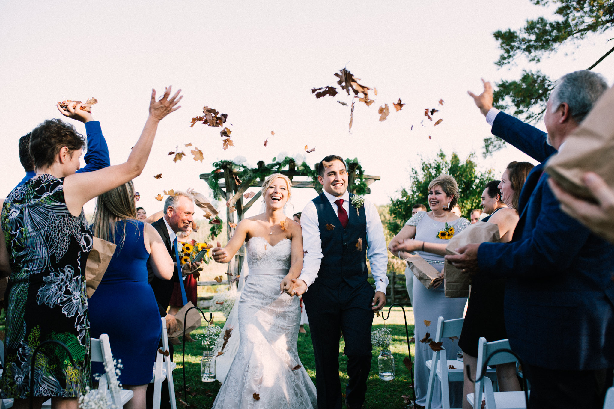 bride and groom walking down the aisle with leaves thrown in the air