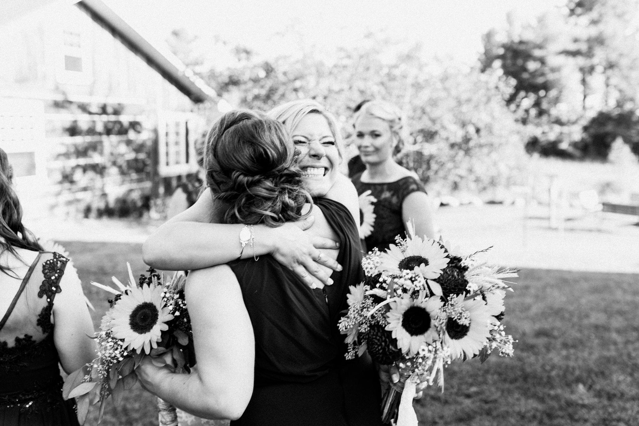 bridesmaid hugging bride after ceremony