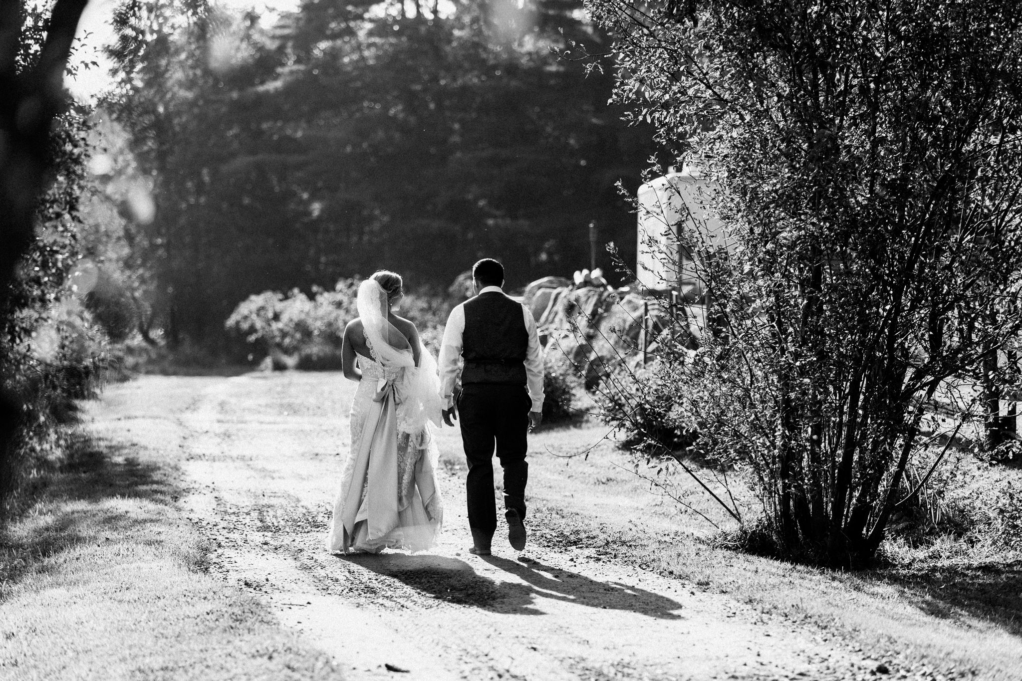 bride and groom walking down a dirt path