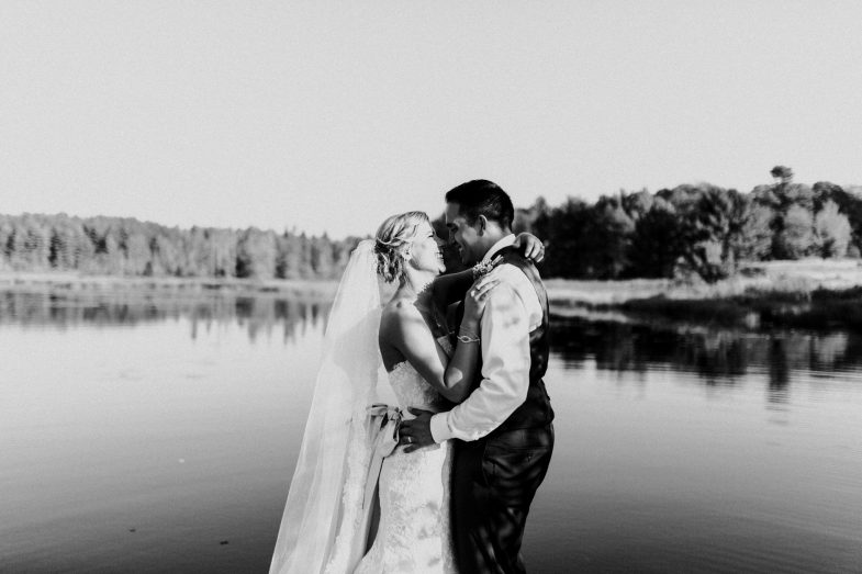 bride and groom standing on a dock looking at each other