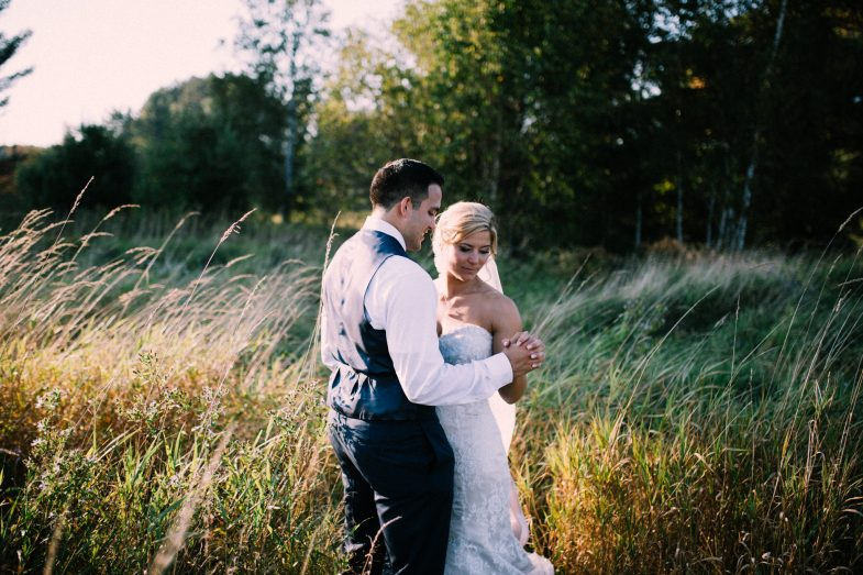 bride and groom holding hands in a field during sunset
