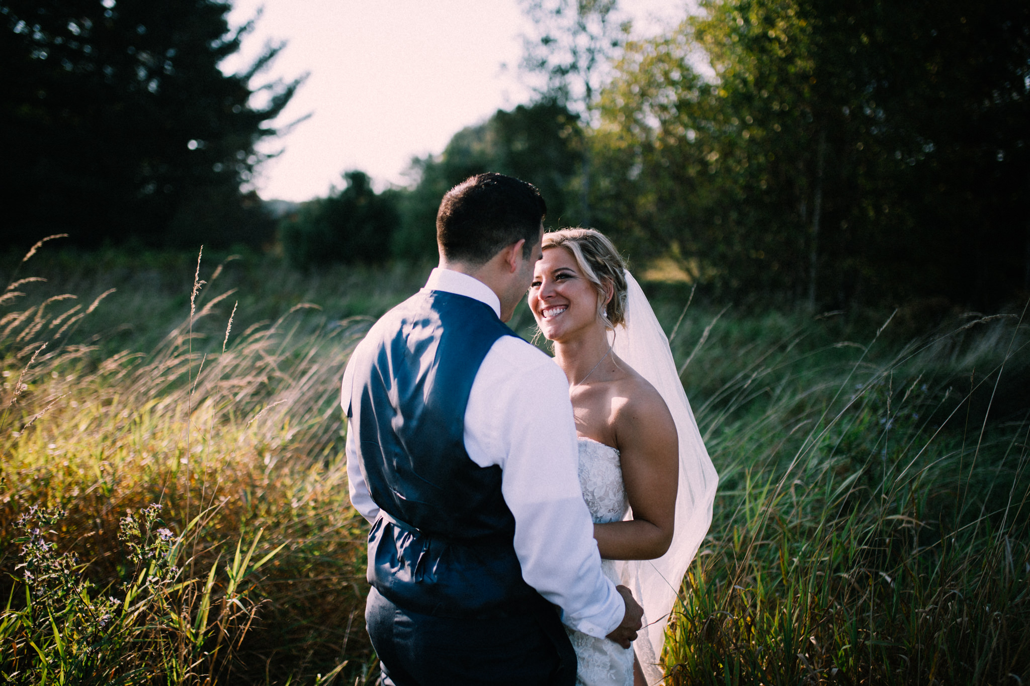 bride smiling at her husband in a field at brooklands farm