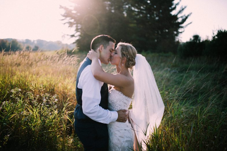 bride and groom sharing a kiss in a field during sunset