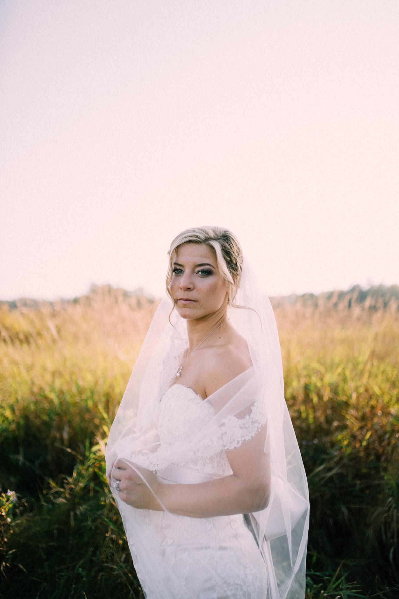 bride looking into camera in a field