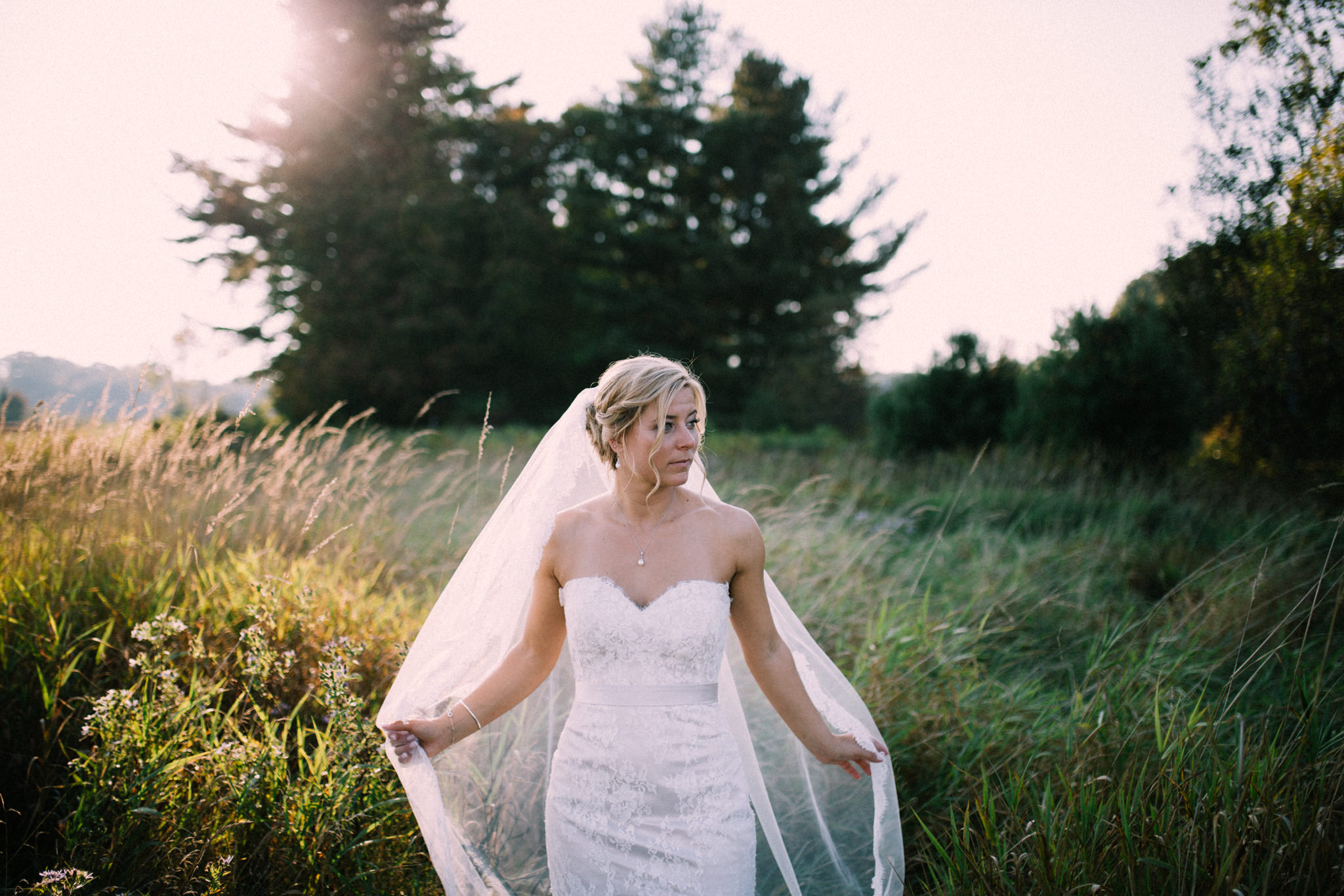 bride holding her veil while walking through a field