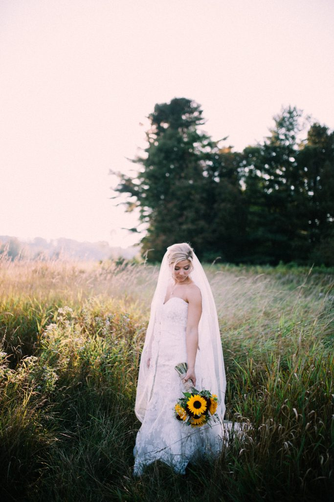 bride looking at her bouquet while standing in a field