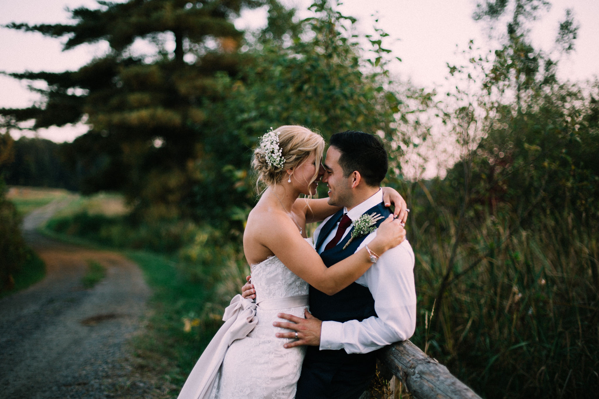 groom leaning on a fence while bride is hugging him