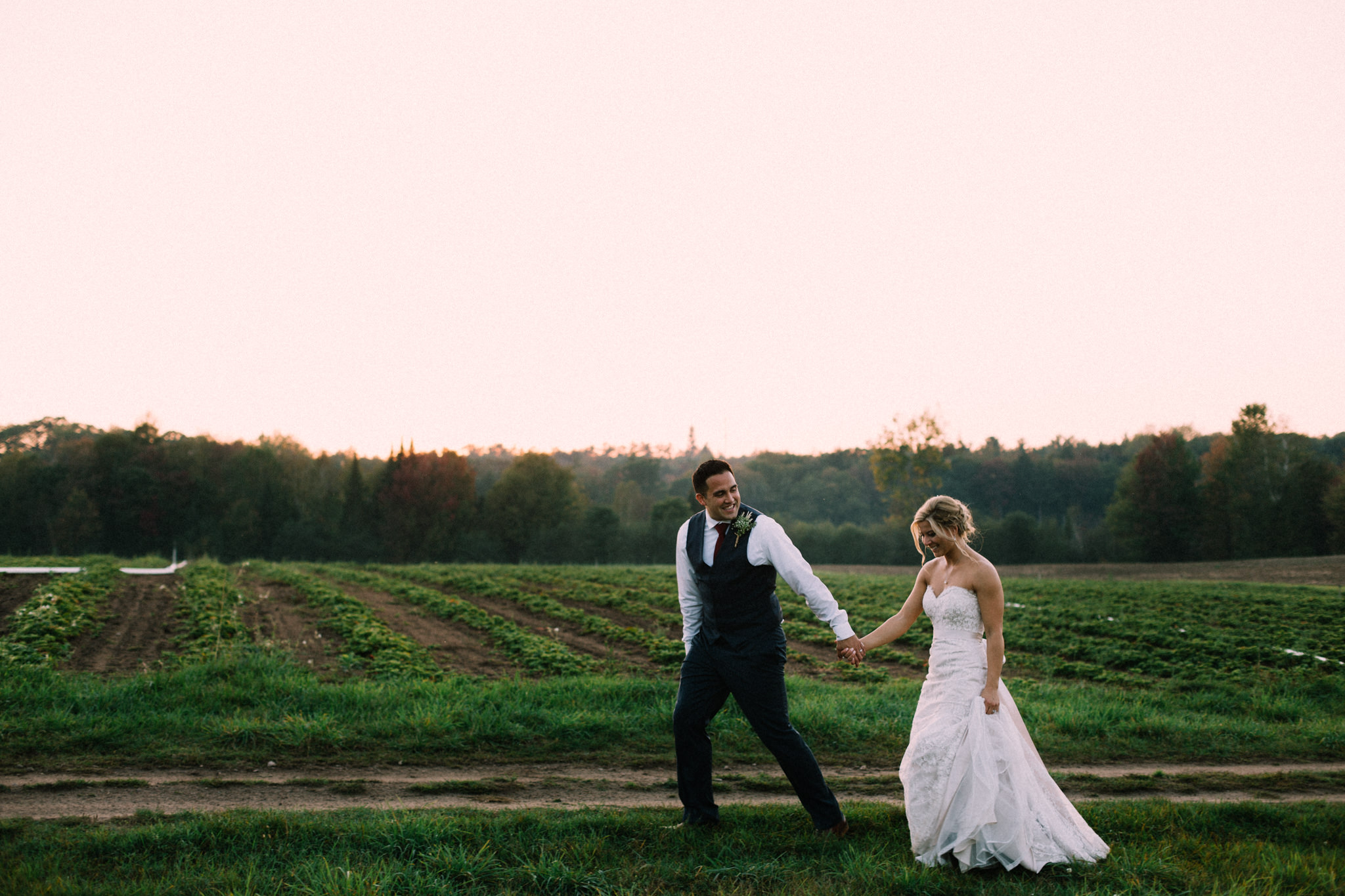 bride and groom walking through the fields at a farm at brooklands farm