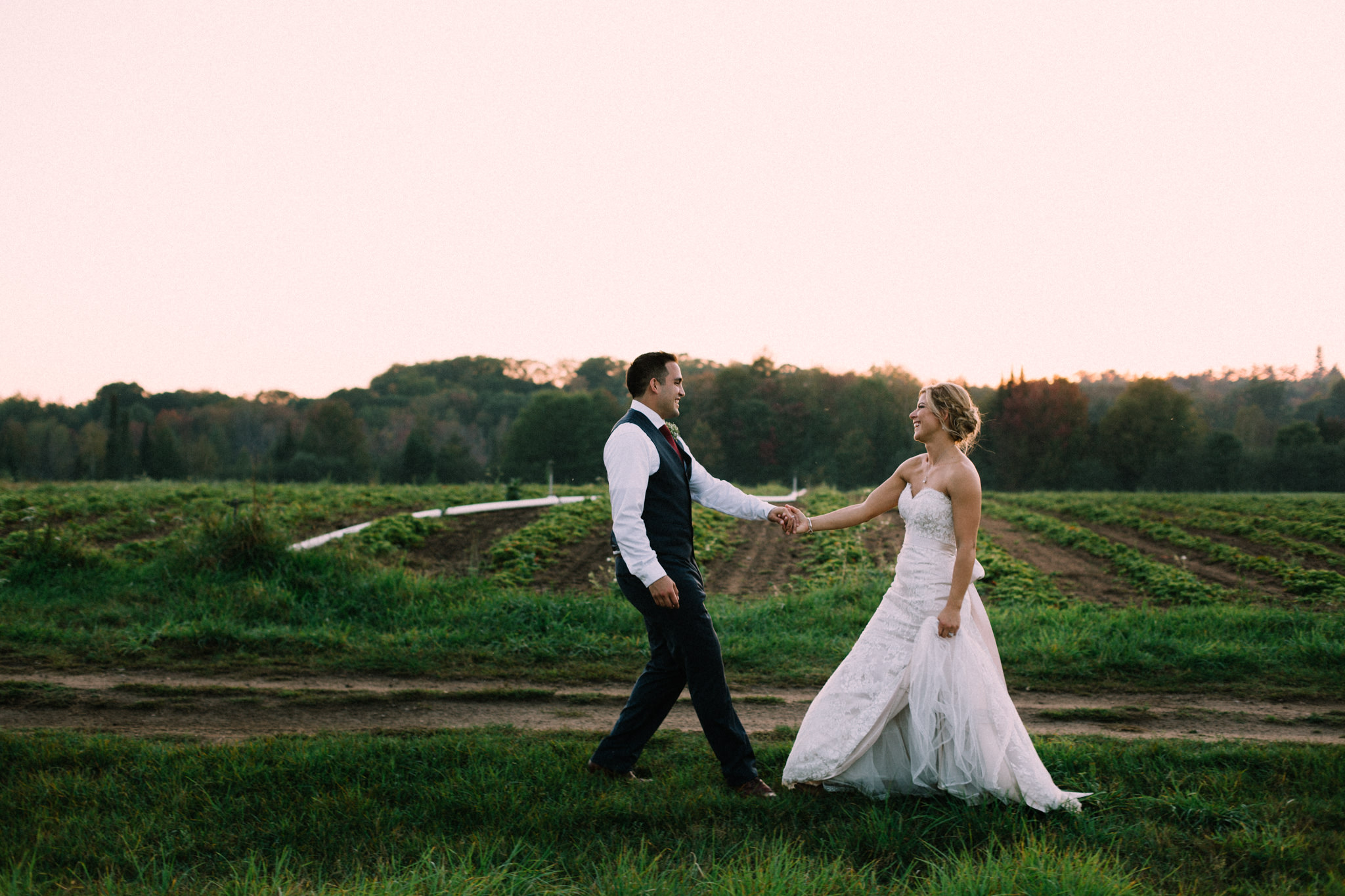 bride and groom dancing on a farm field