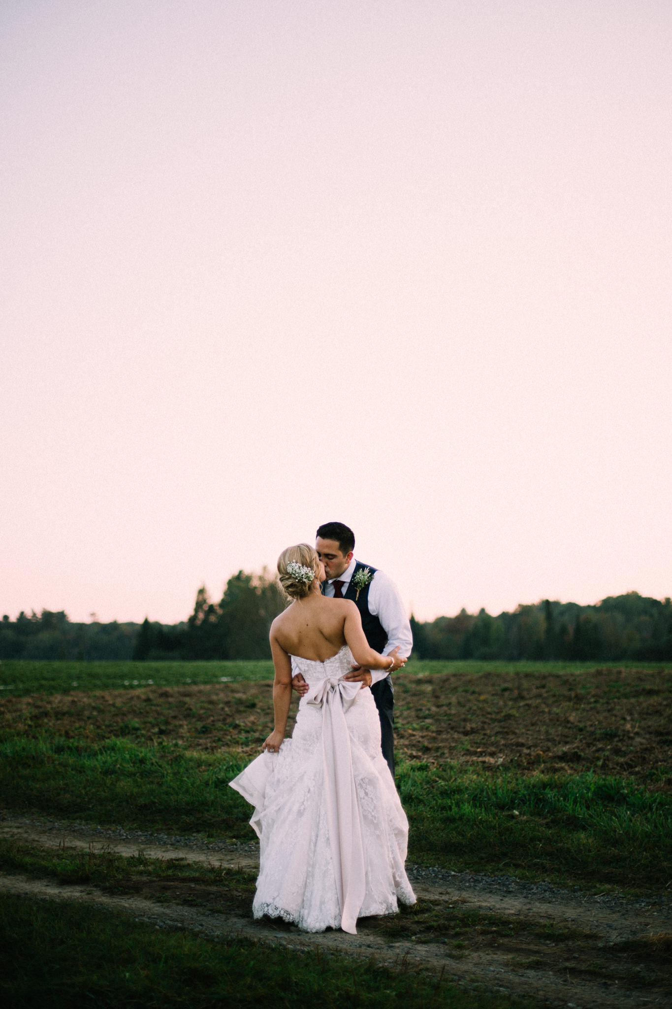bride and groom kissing on a farm field