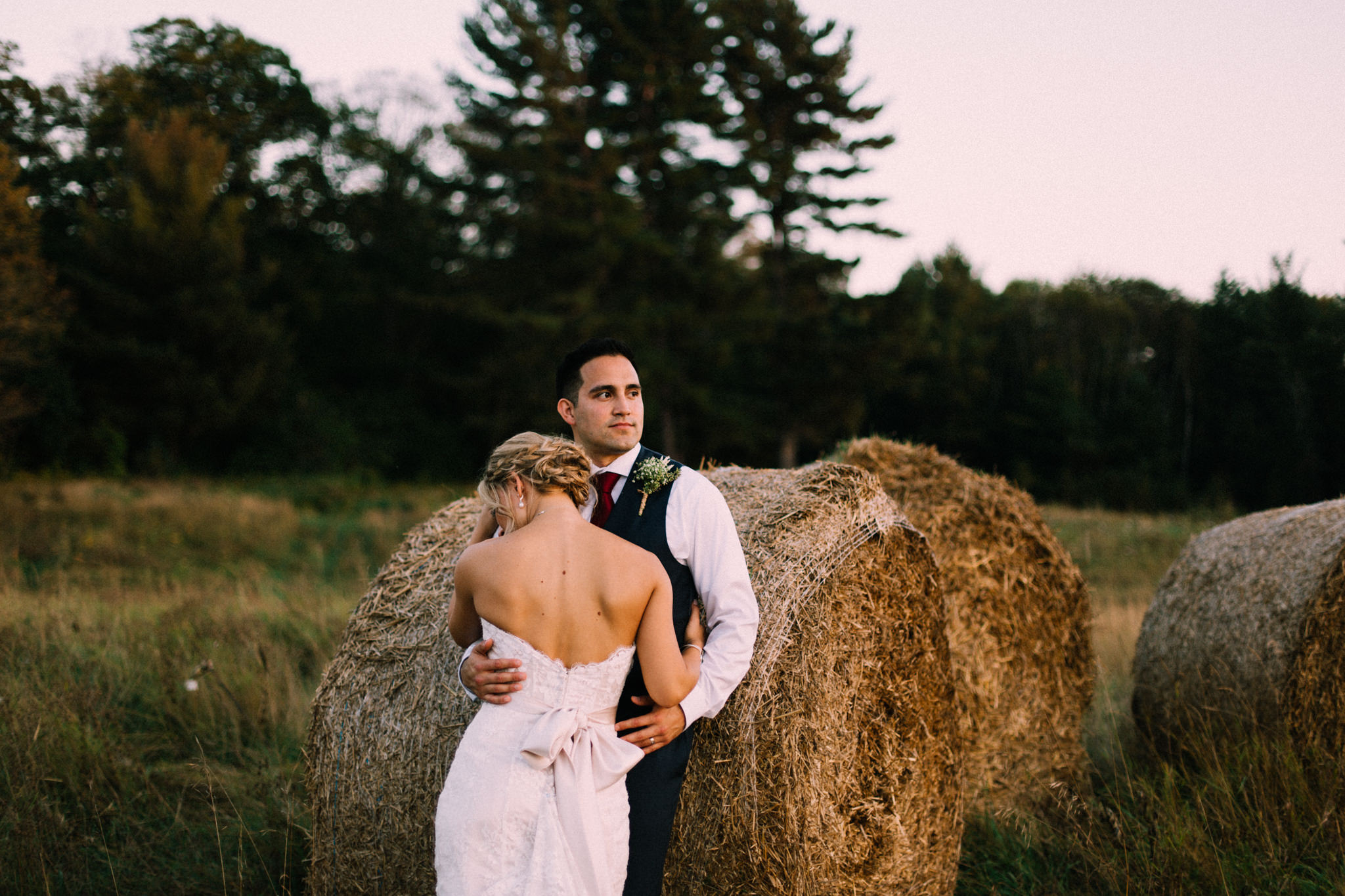 bride and groom leaning on a haystack
