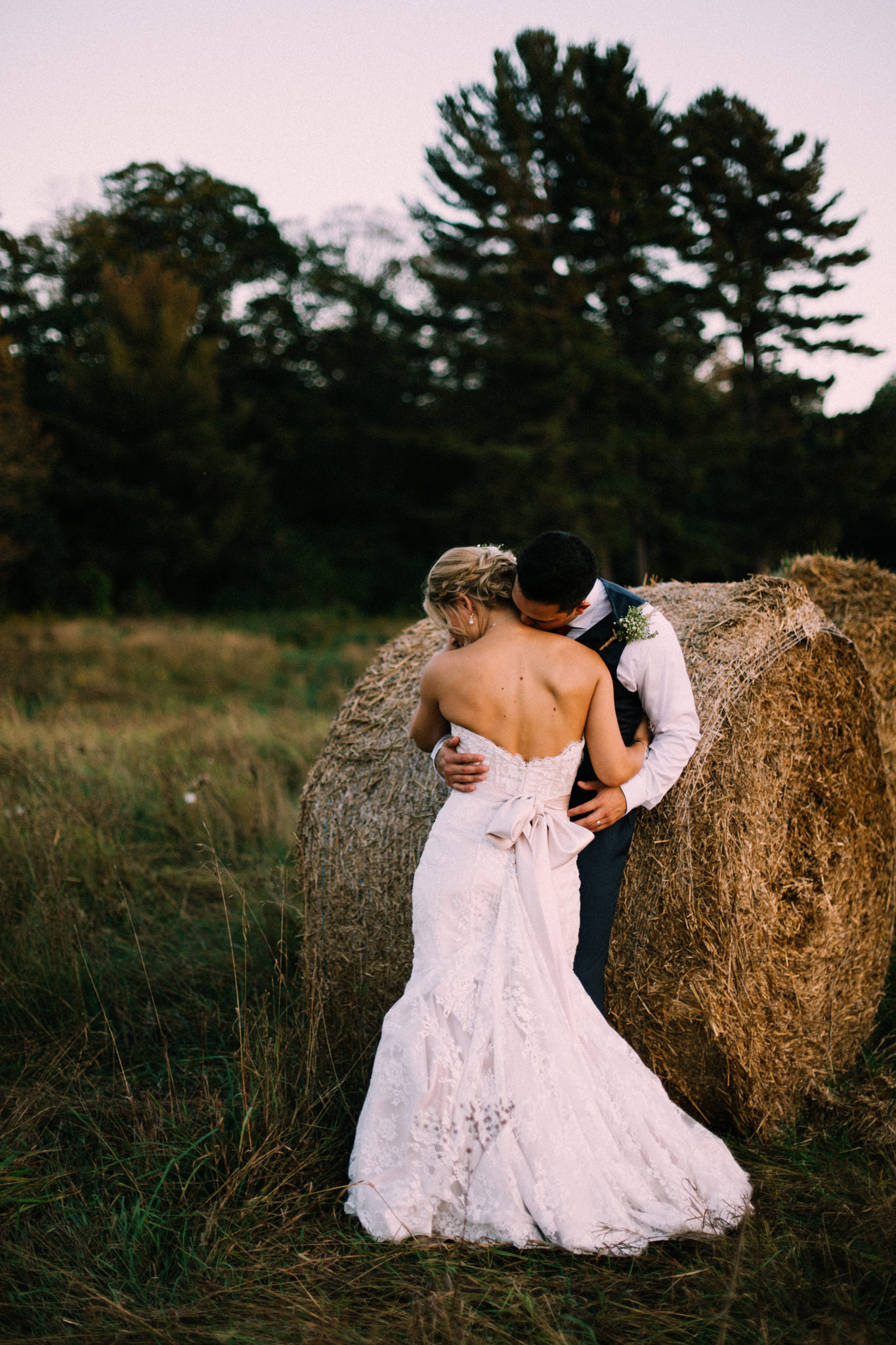 groom kissing bride on the neck in a farm field
