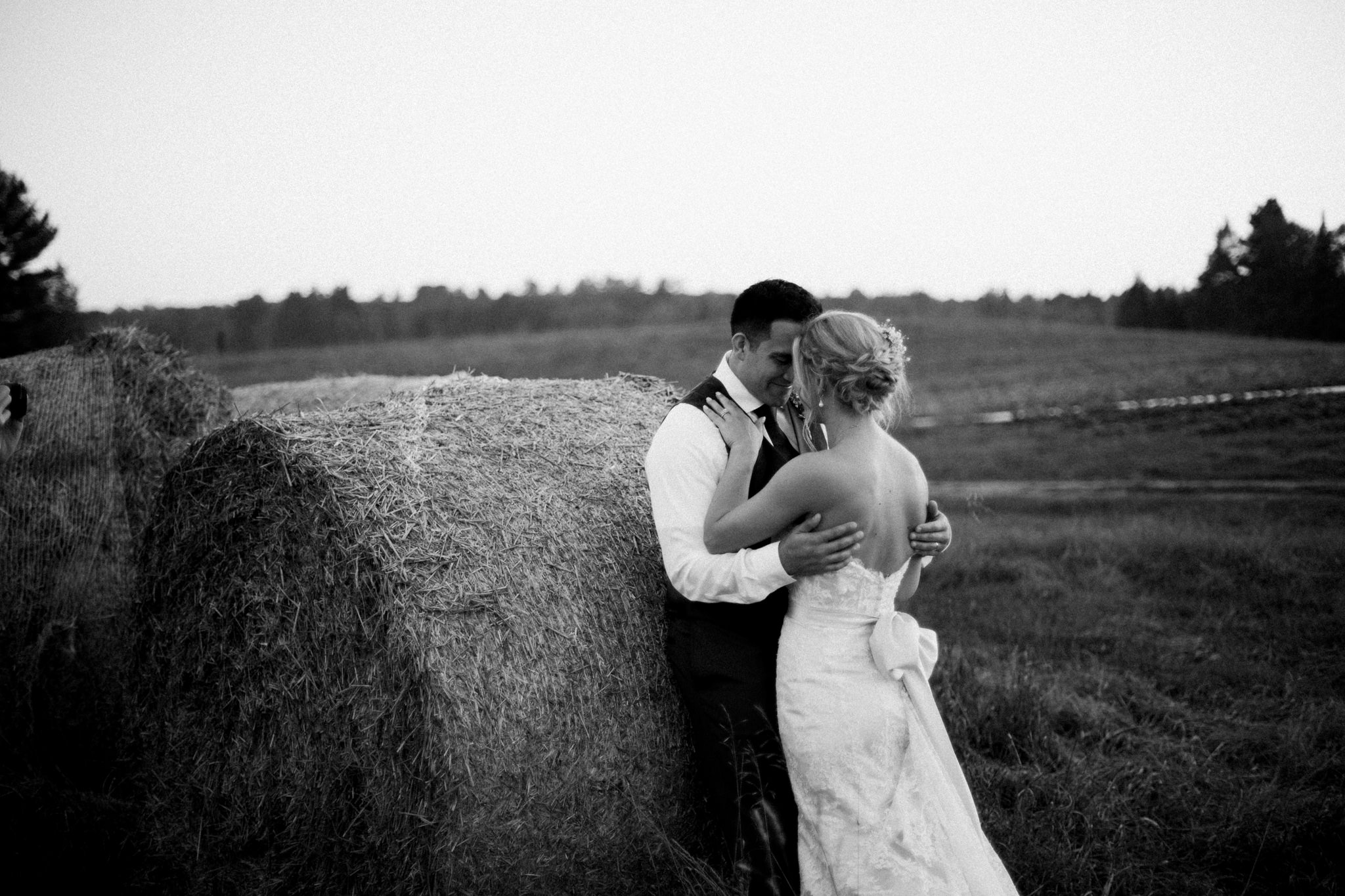 bride and groom embracing in front of a haystack
