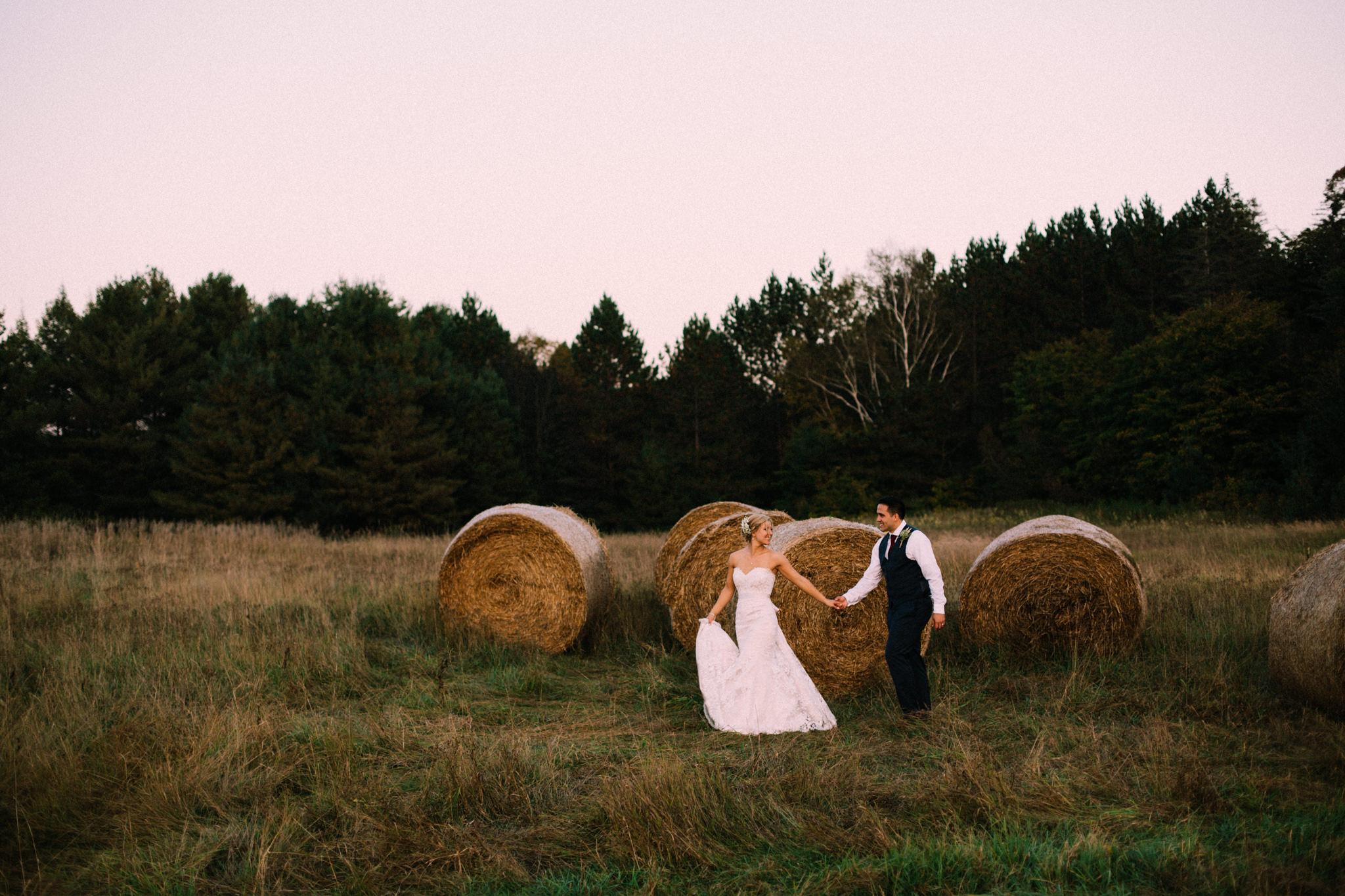 bride leading groom through a hayfield