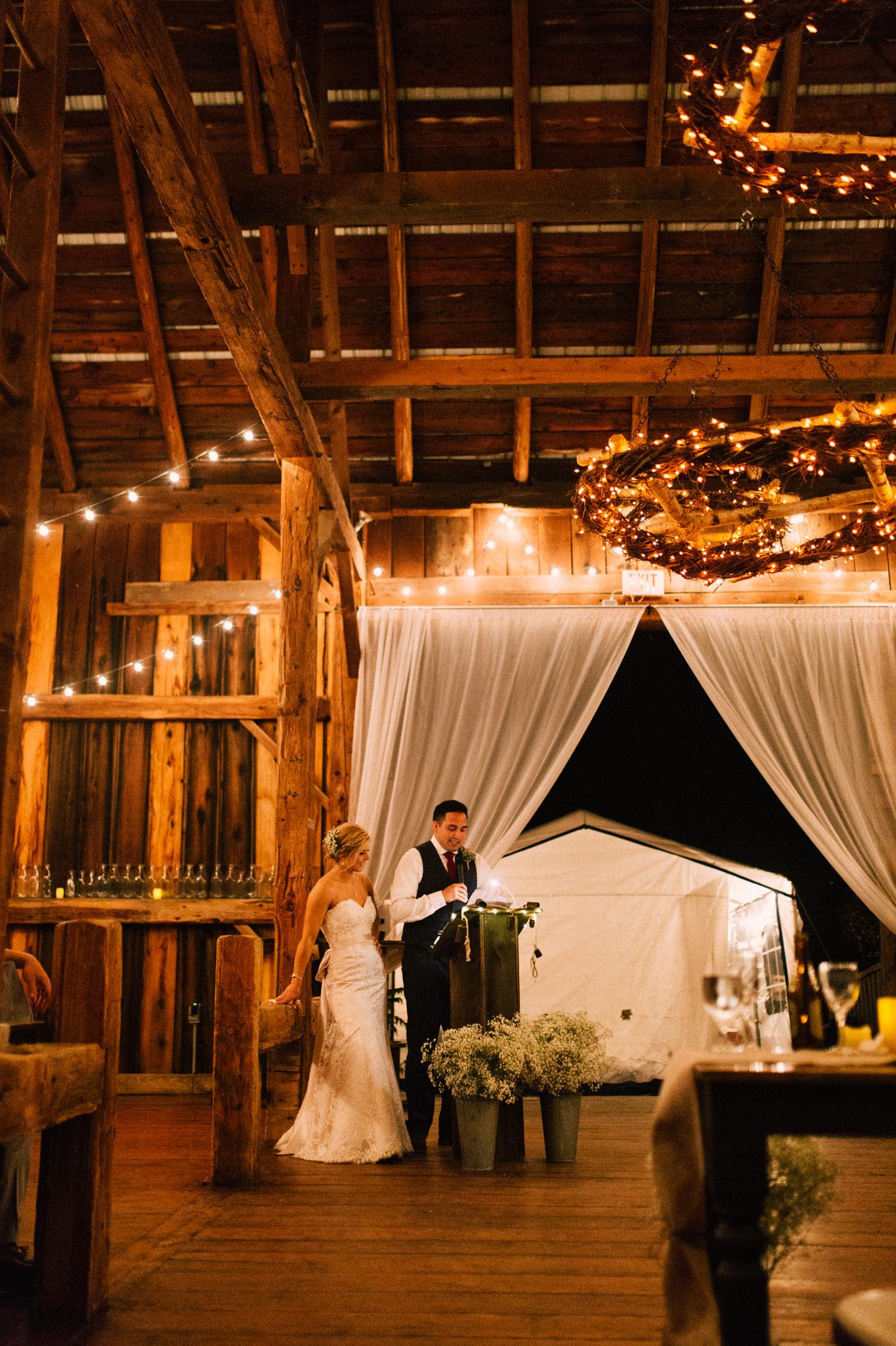 groom giving speech in a barn