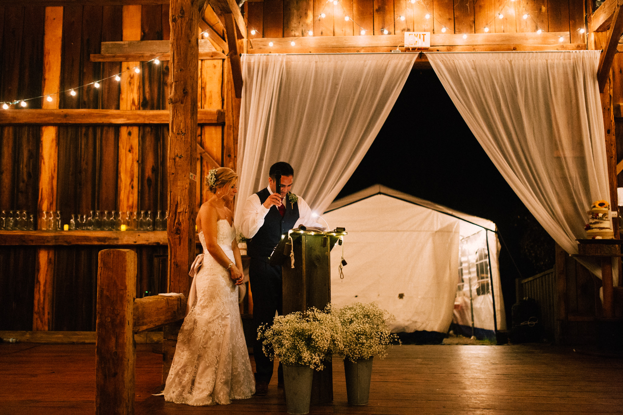 bride and groom giving speech in a barn