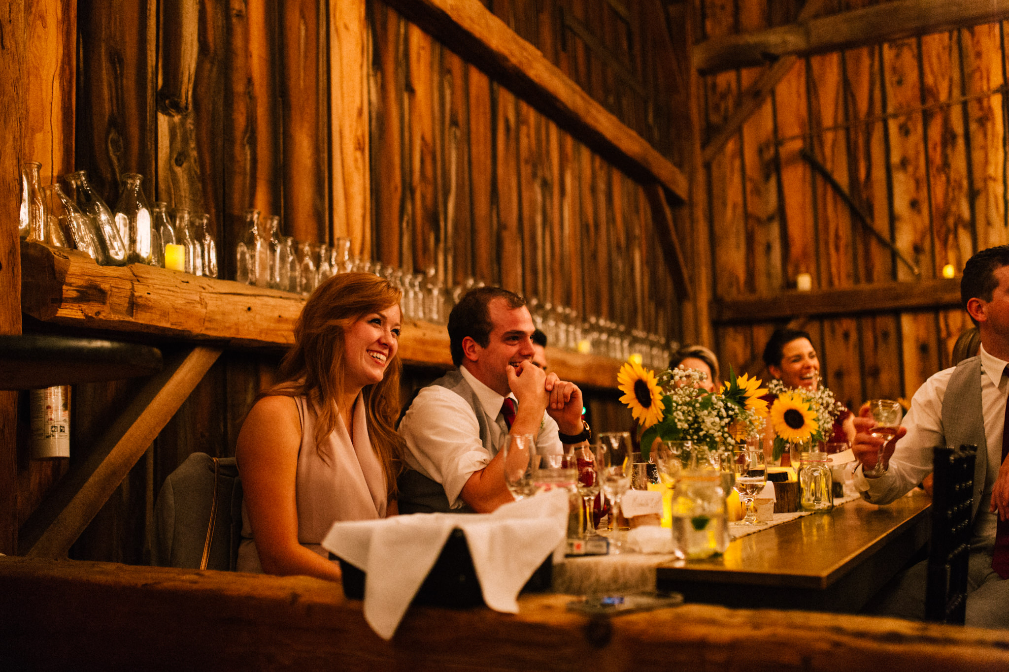 bridesmaid smiling during a speech in a barn