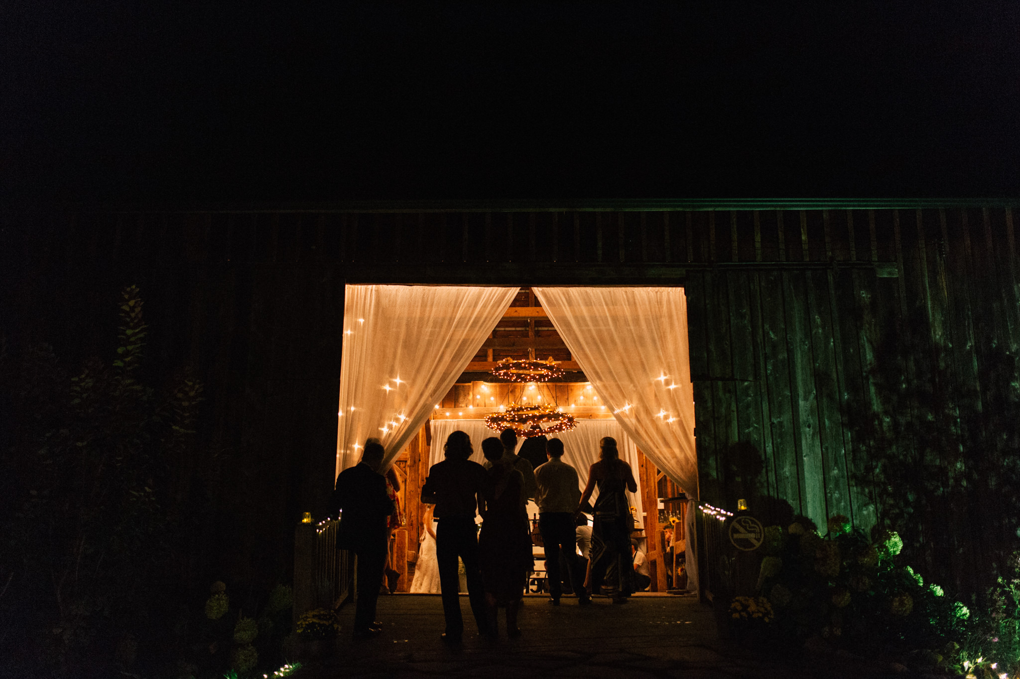 silhouette of guests at a barn wedding