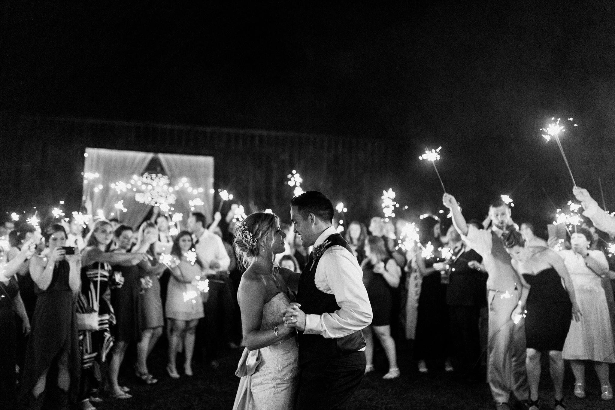 bride and groom dancing under sparklers