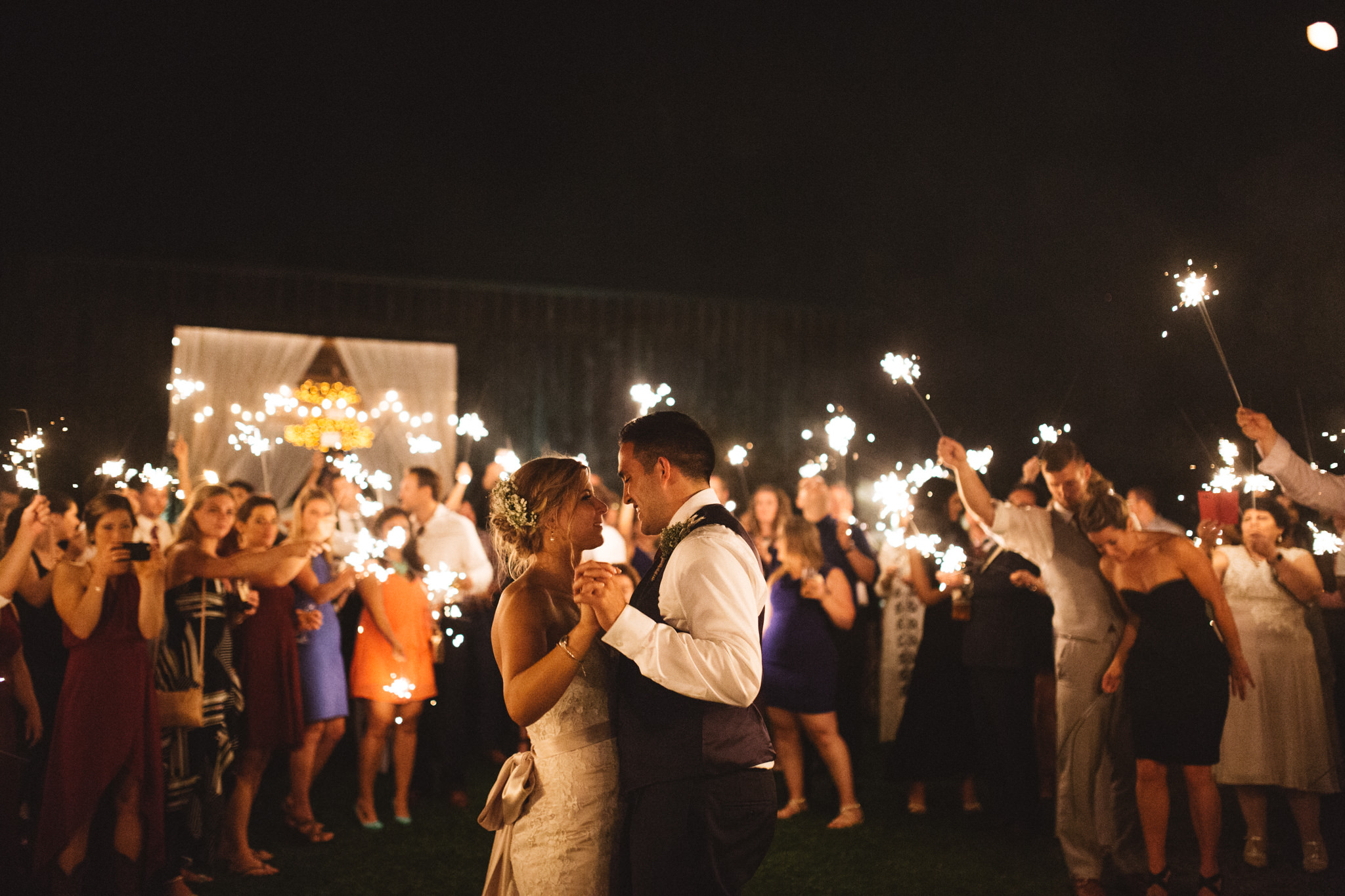 bride and groom dancing under sparklers in a field