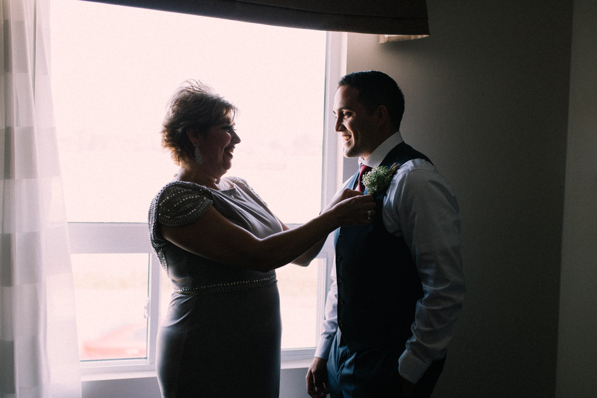 mother helping groom with boutonniere