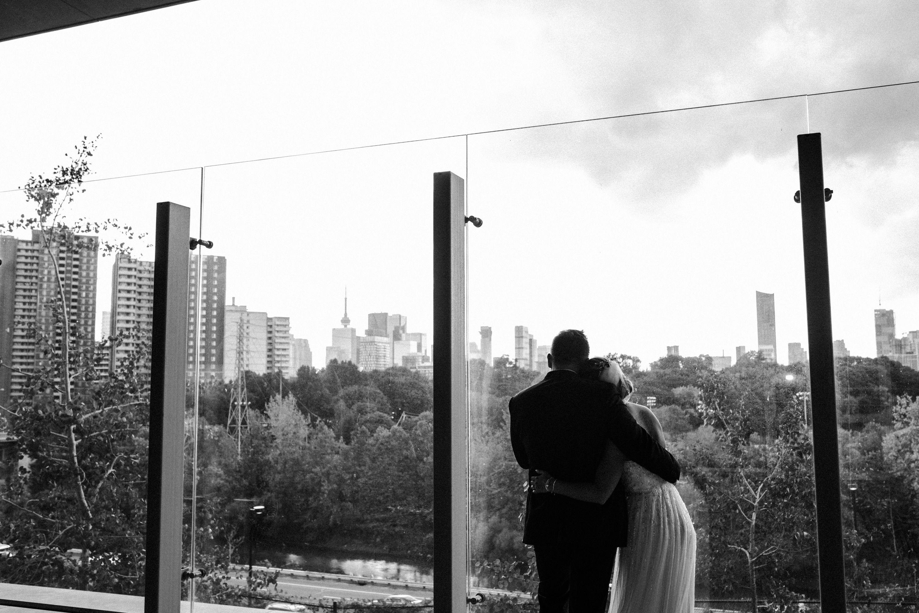 bride and groom holding each other looking over toronto skyline