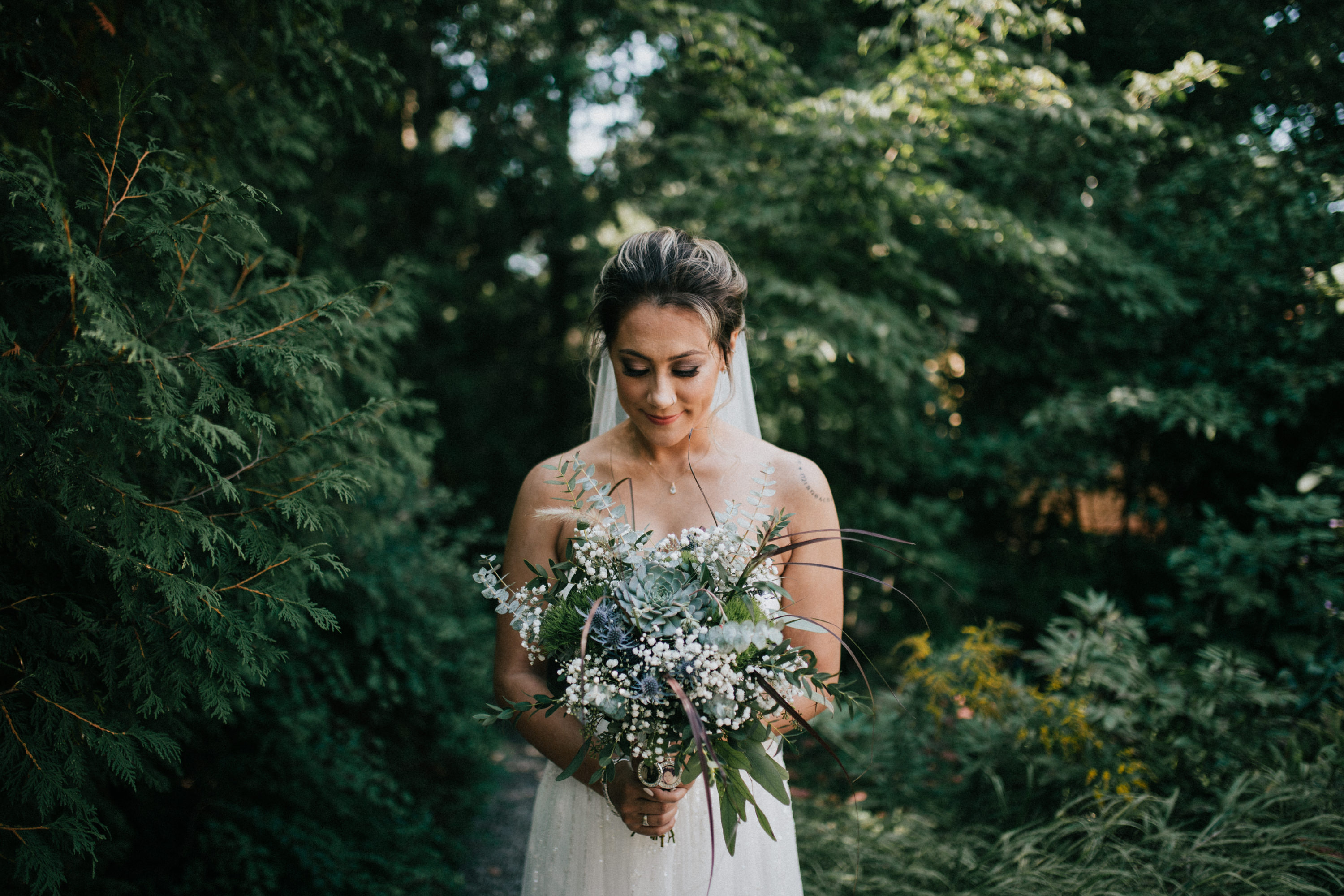 bride looking at her flowers in a garden