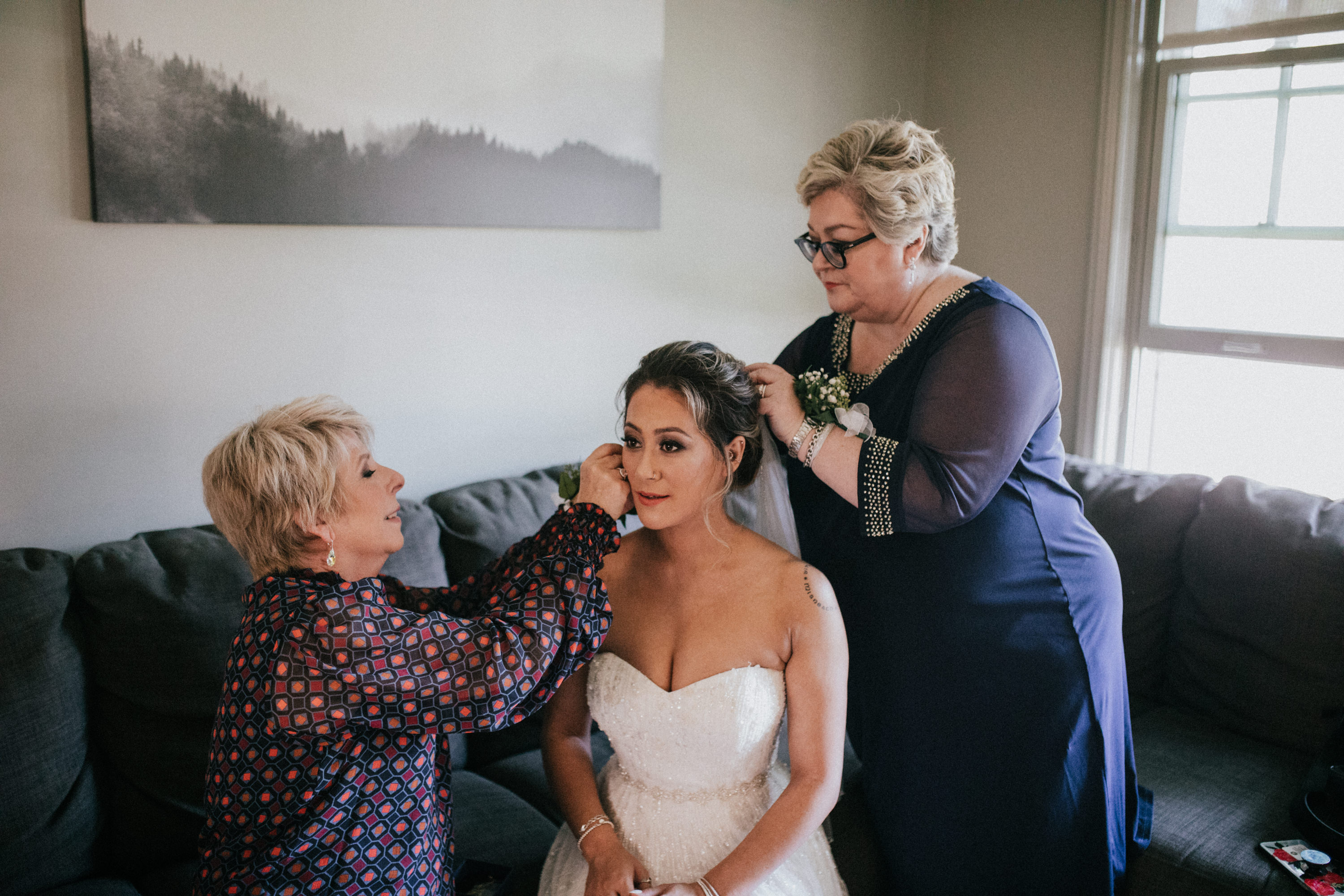 bride getting help from mothers putting on accessories