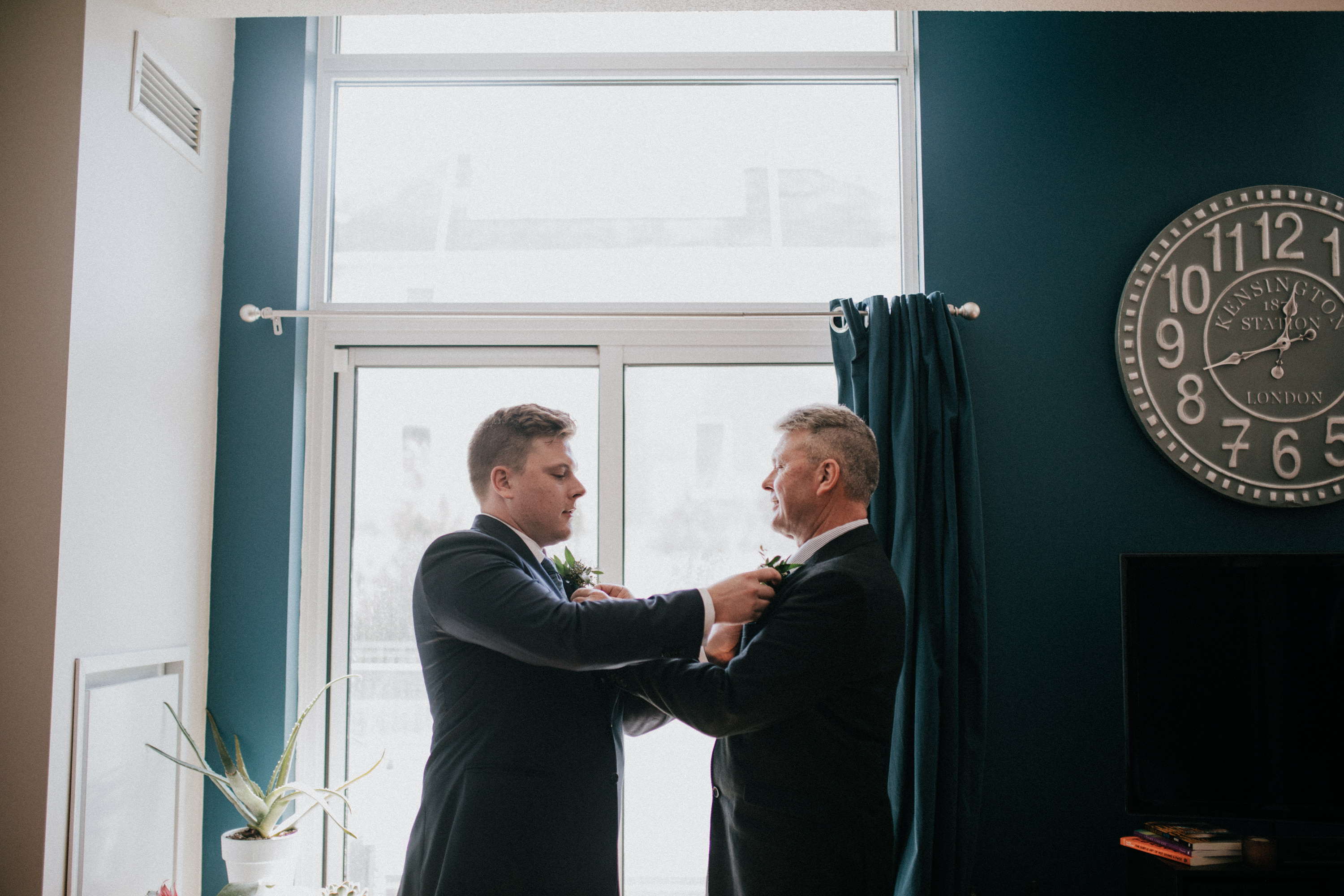 groom and father help each other with boutonnière