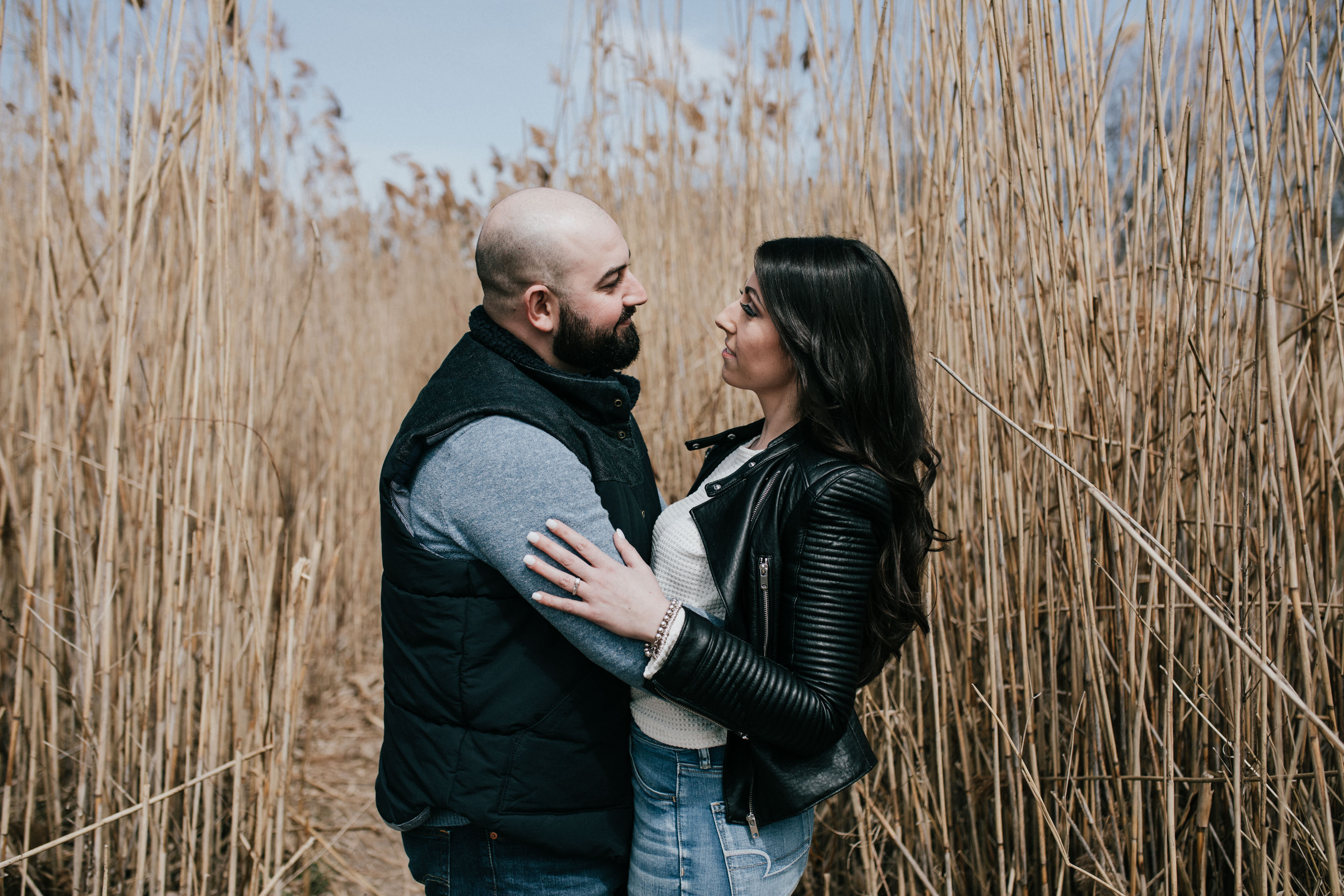 man and woman embracing in a hay field during a spring engagement shoot