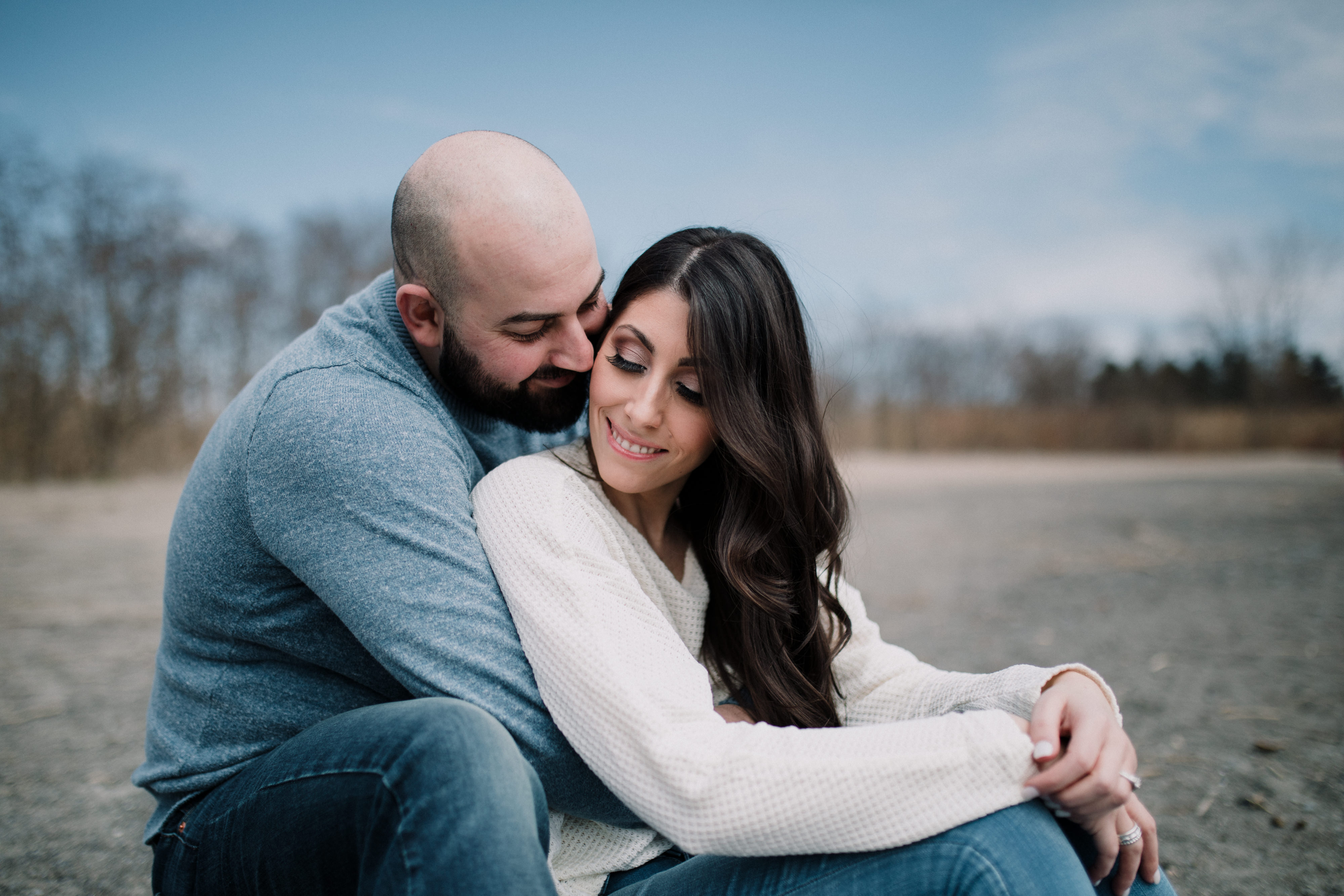 man hugging woman from behind on beach during a spring engagement shoot