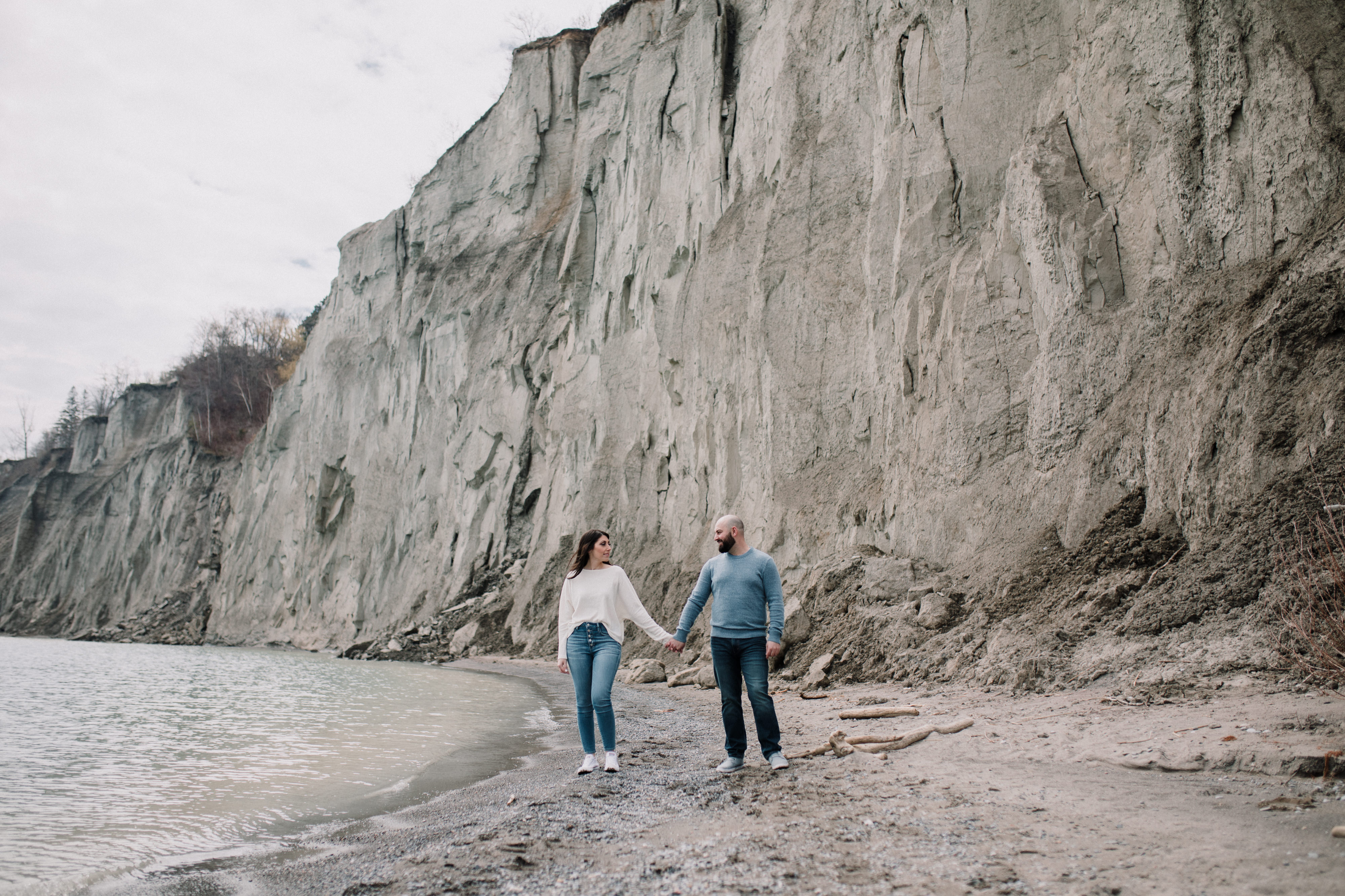 engaged couple holding hands by a cliff during a spring engagement shoot