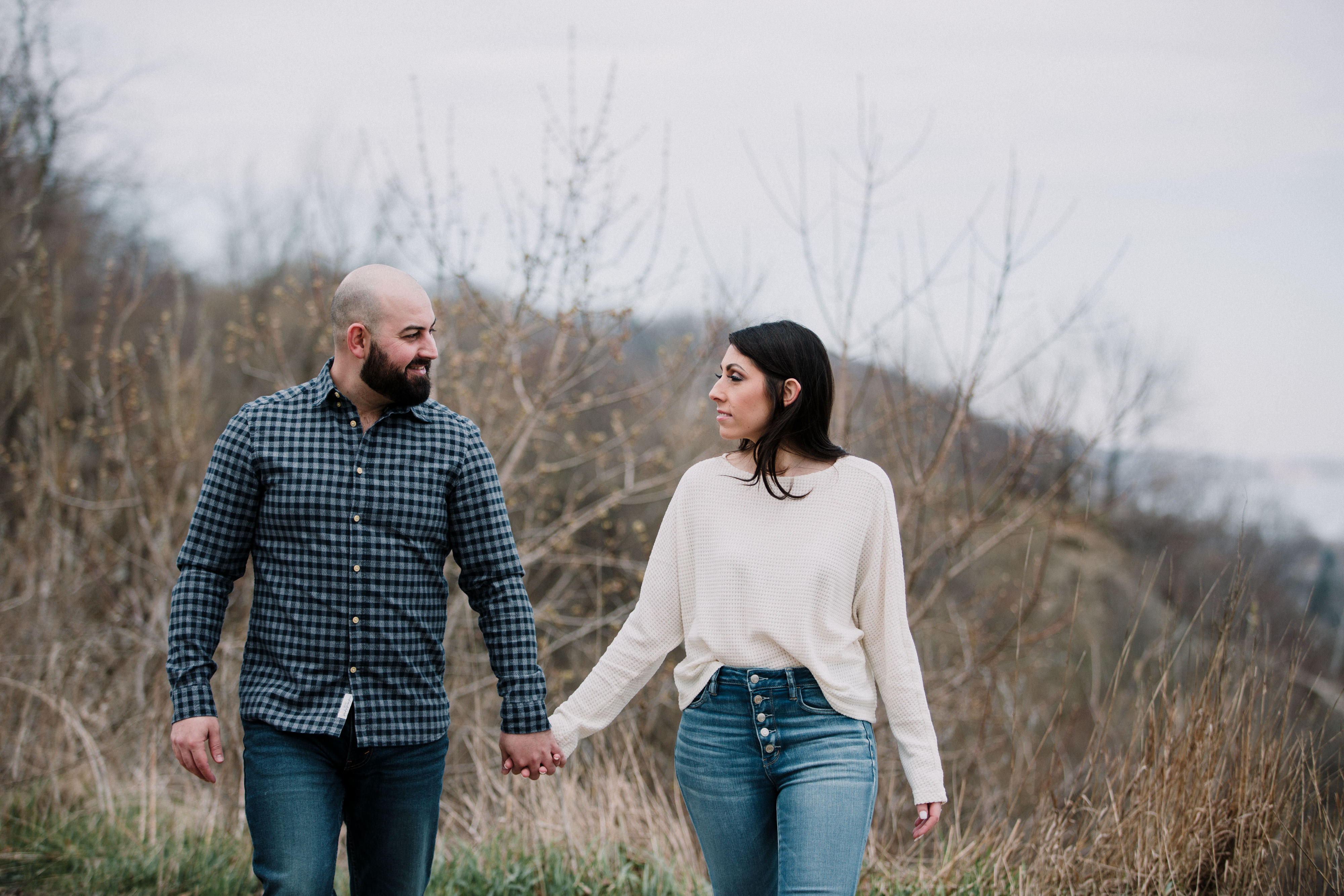 engaged couple walking with hands held in the fall during a spring engagement shoot
