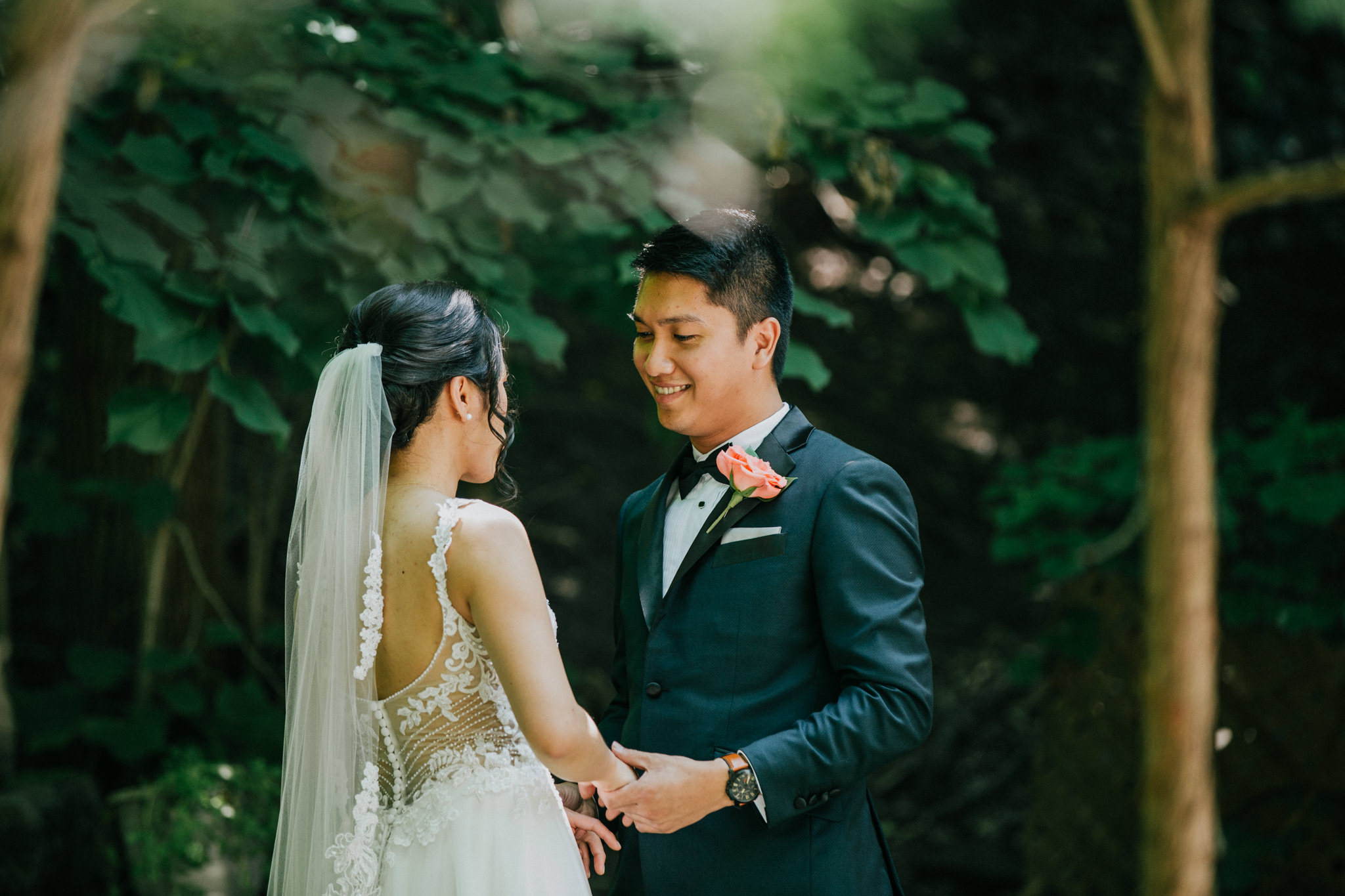 groom smiling at bride in a garden