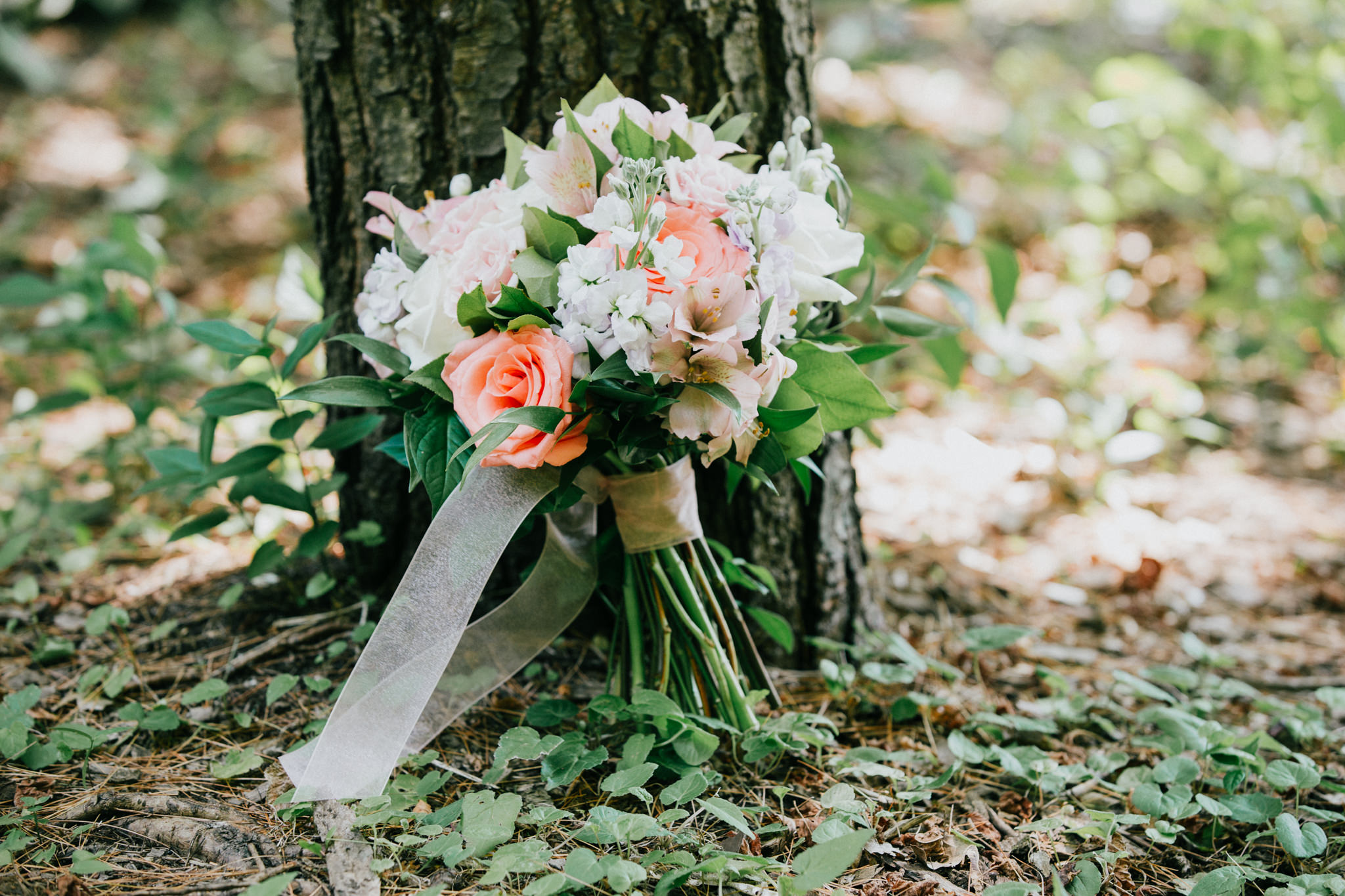 wedding floral bouquet next to a tree