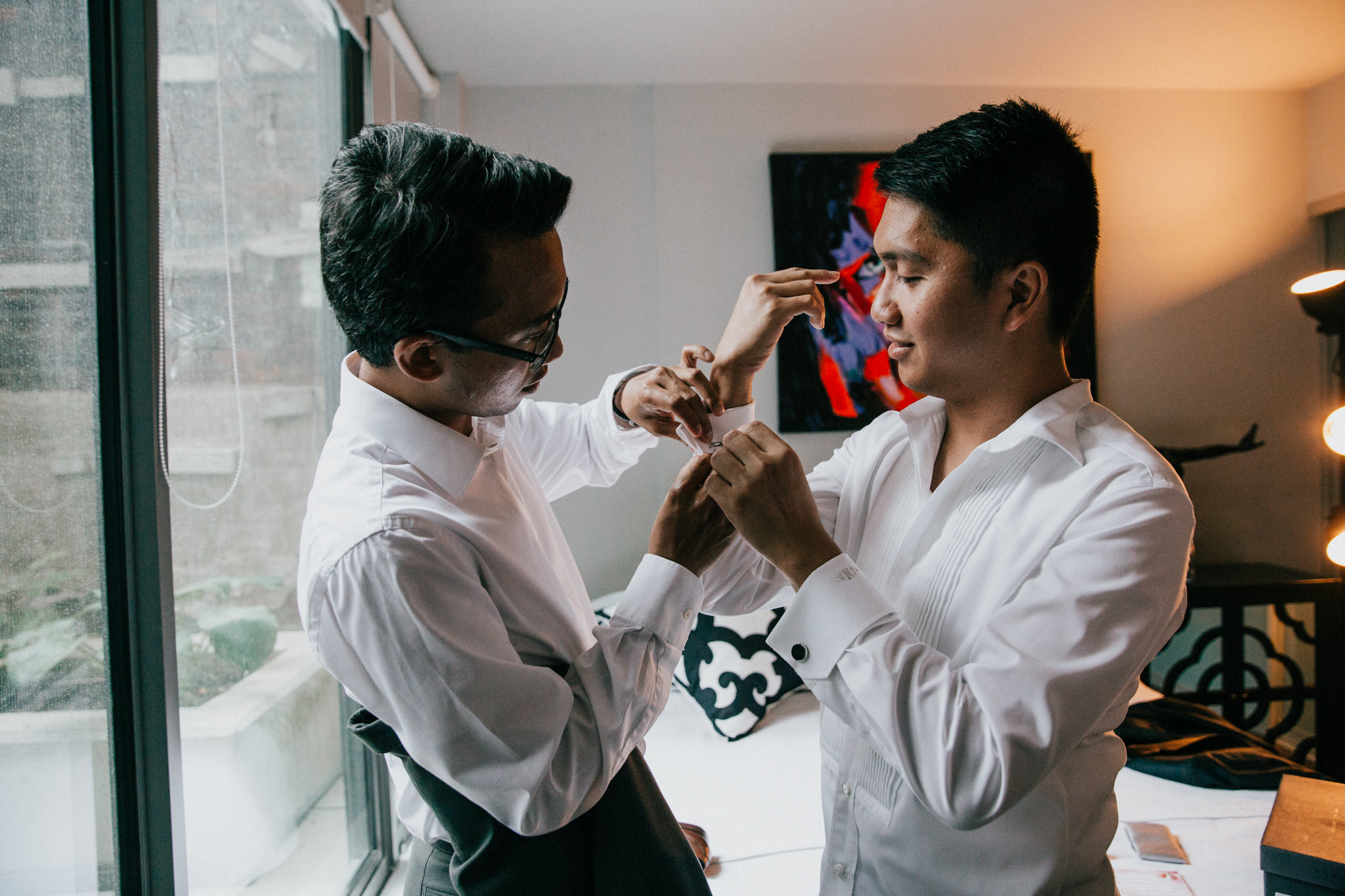 groomsman helping groom with cufflinks