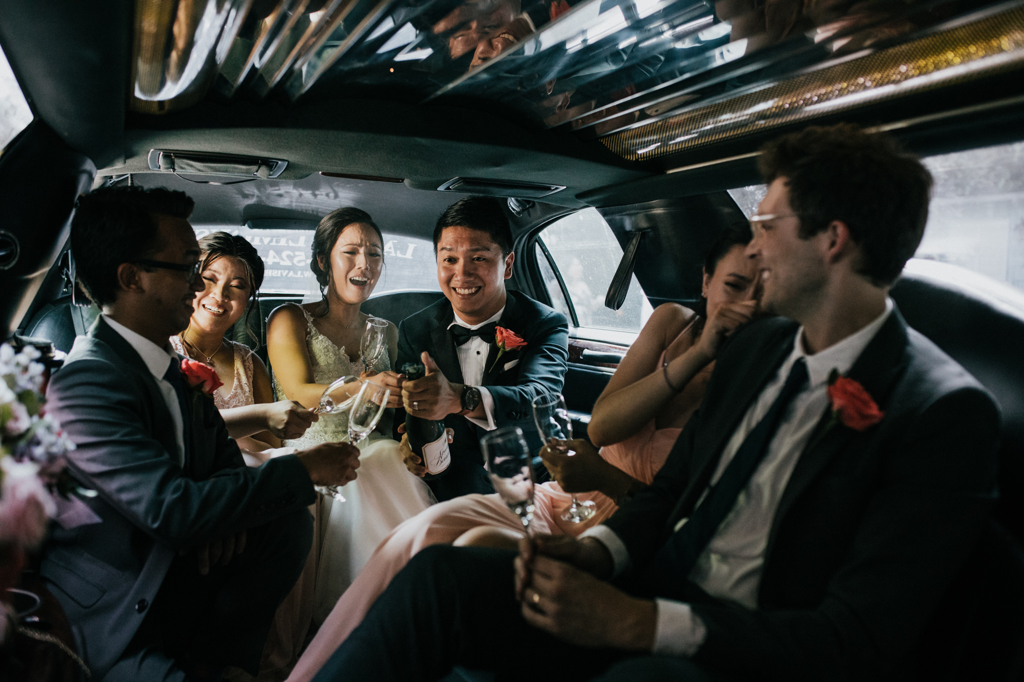 bridal party popping champagne in a limo