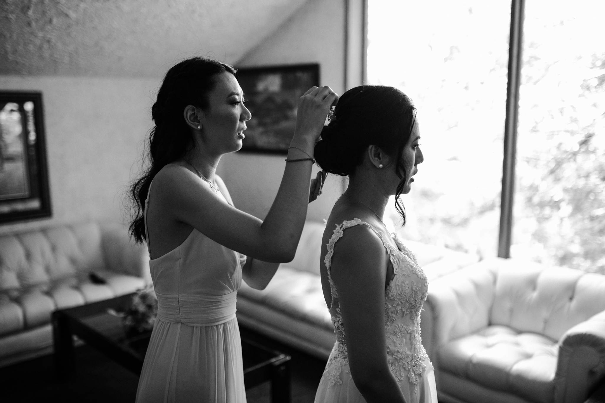 bridesmaid fixing brides hair