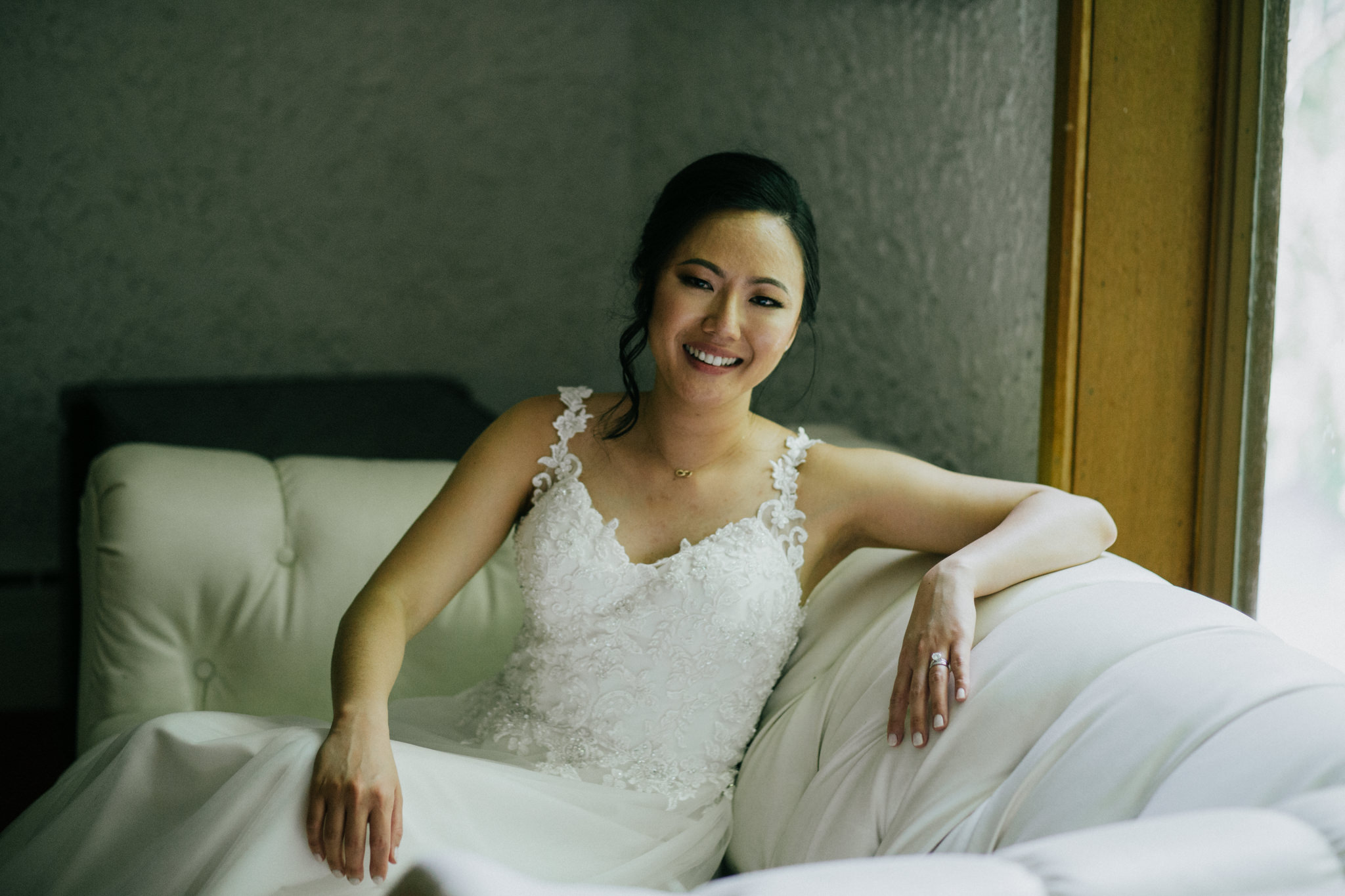 bride smiling while leaning on a couch