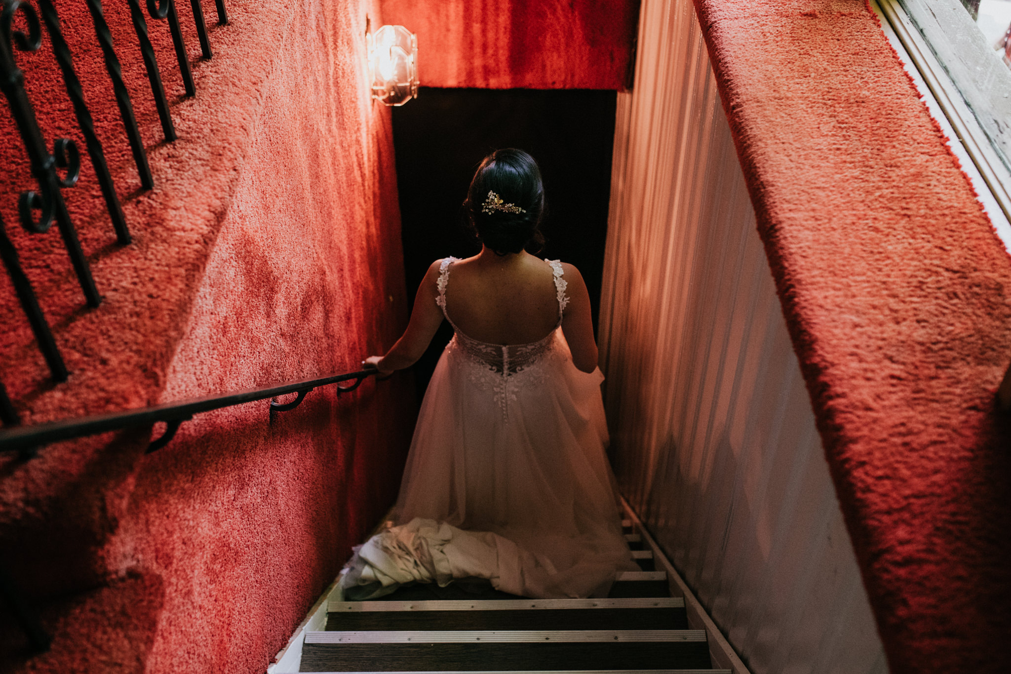 bride walking down a set of red stairs