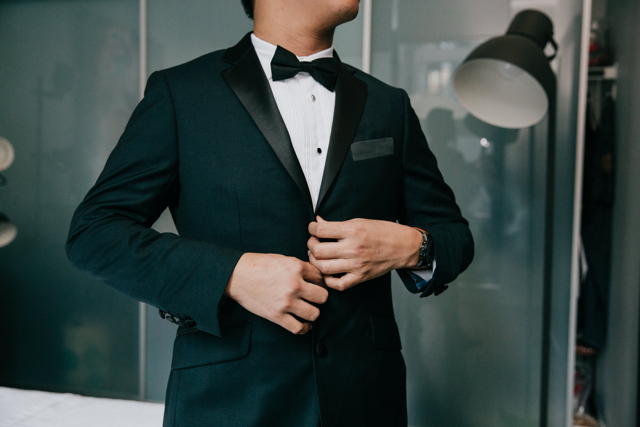 groom buttoning up suit jacket