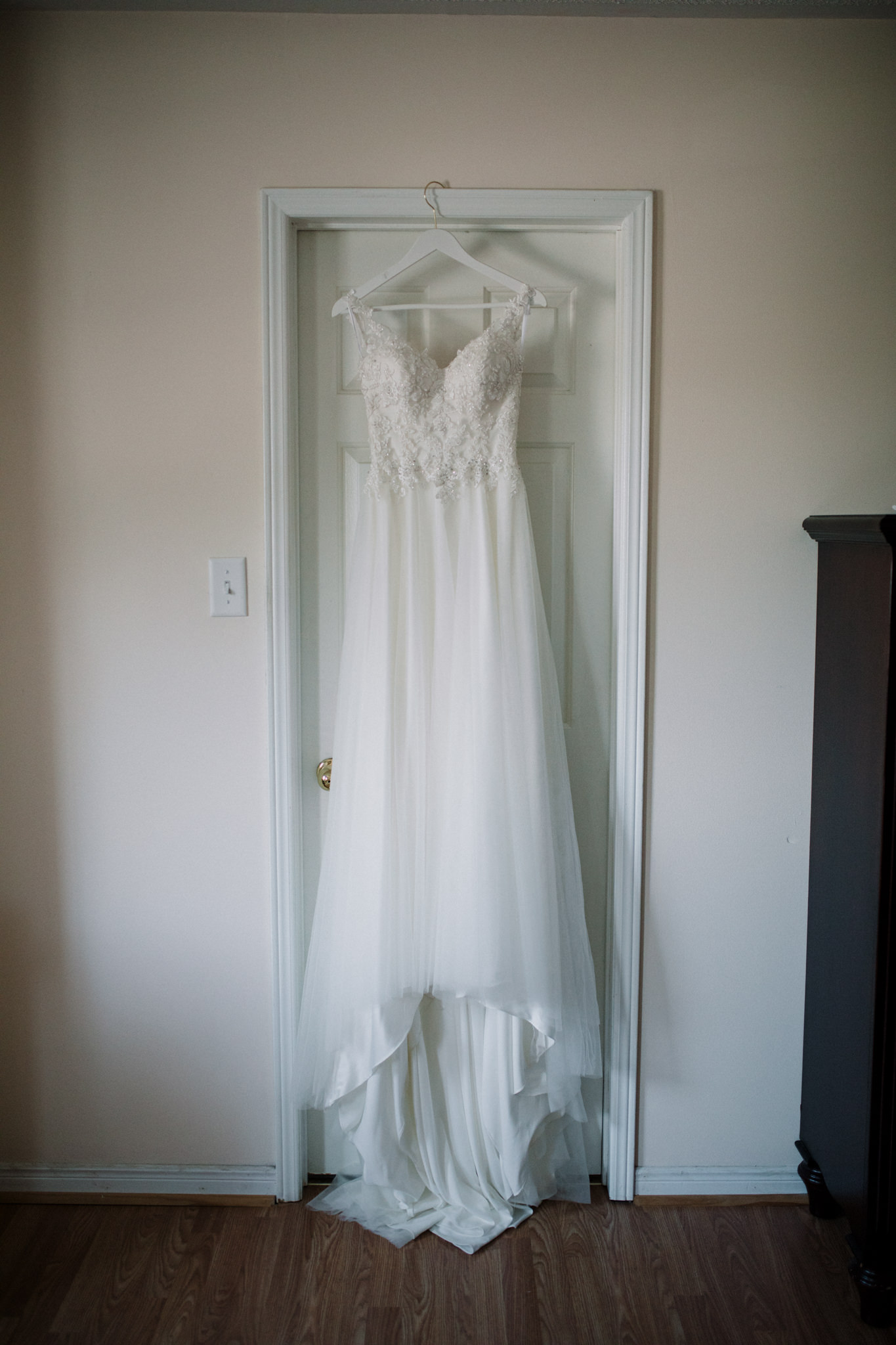 wedding dress hanging over door frame
