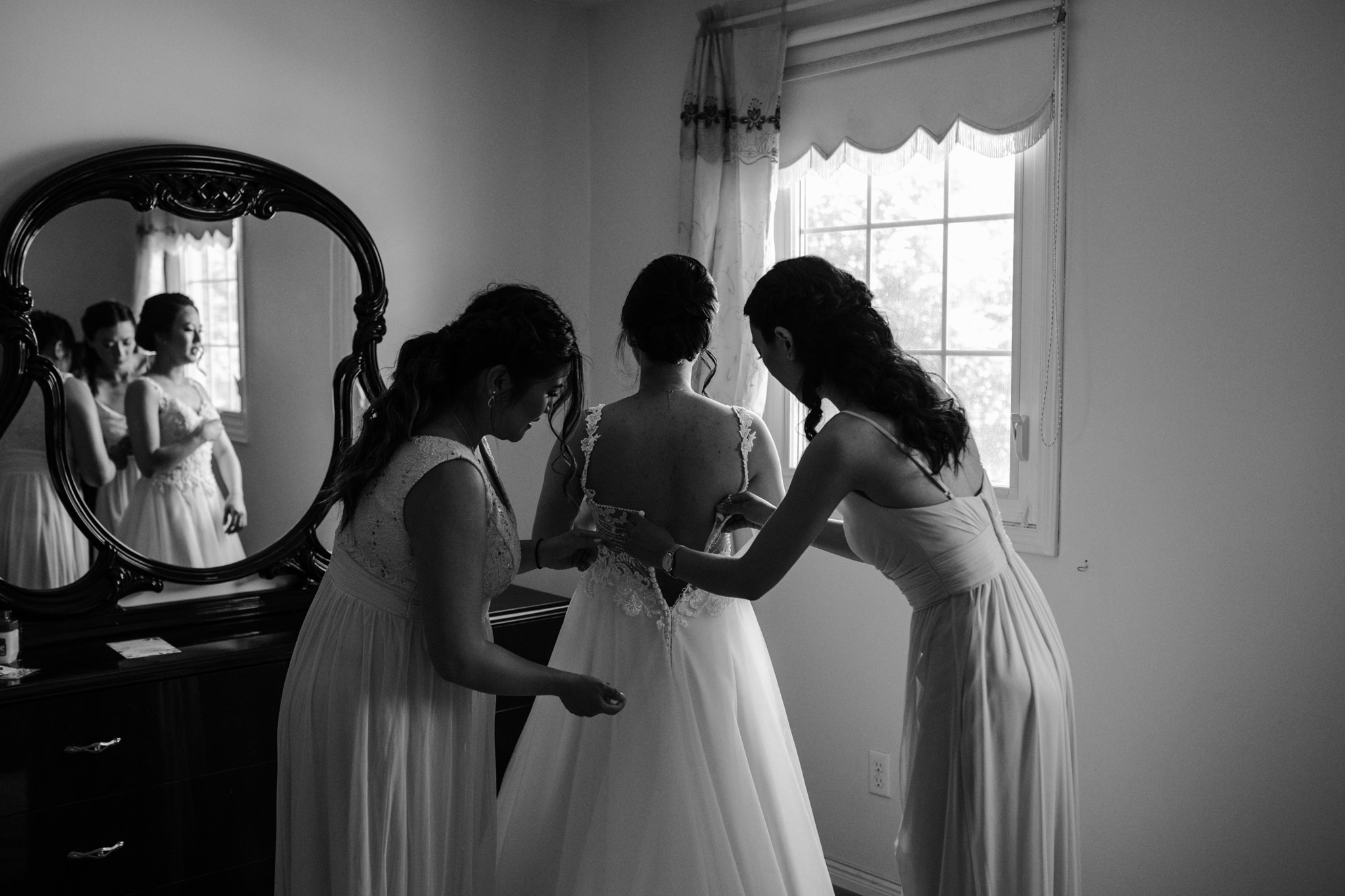 bridesmaids helping bride zip into dress