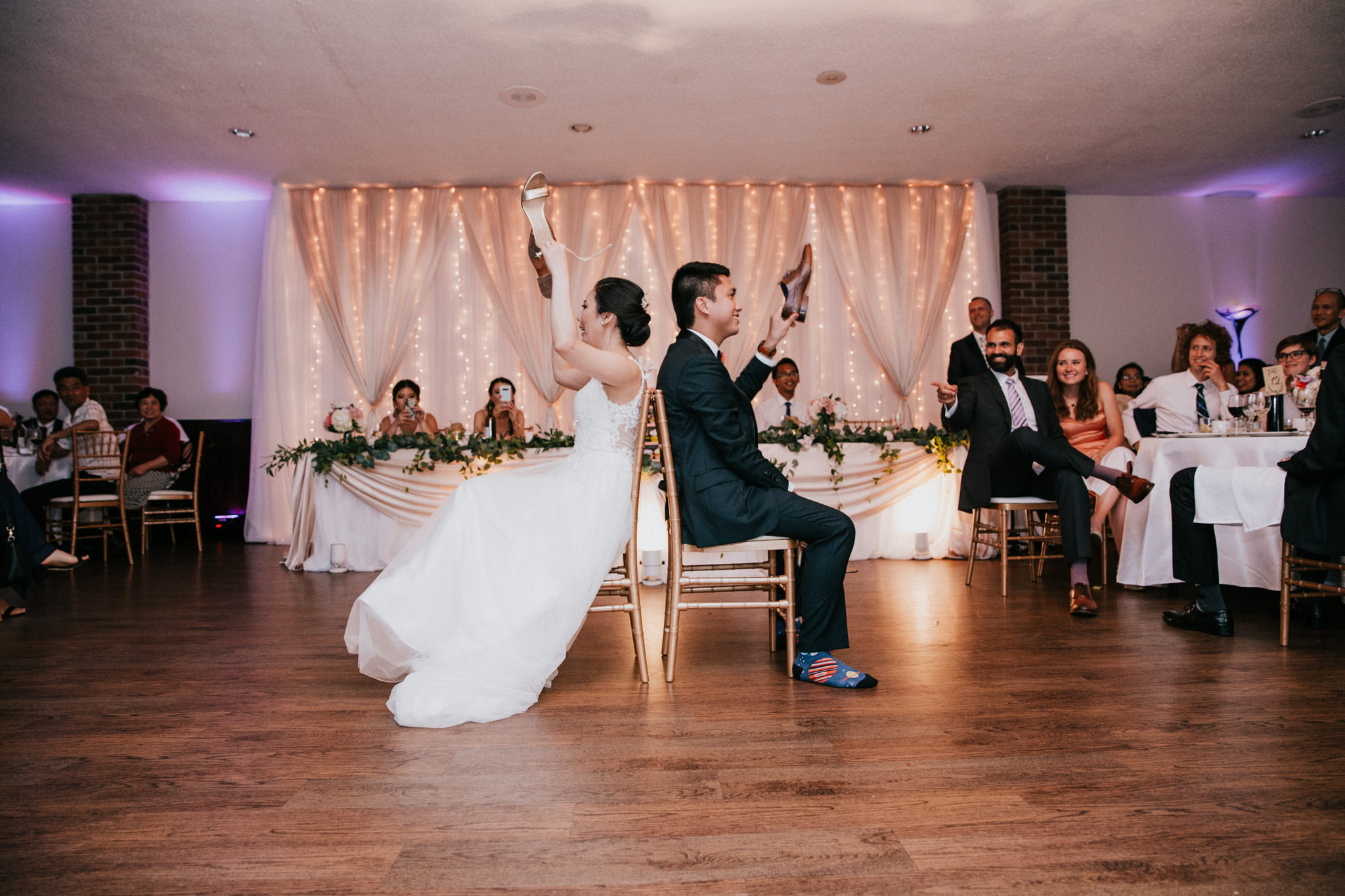 bride and groom holding up shoes during a game